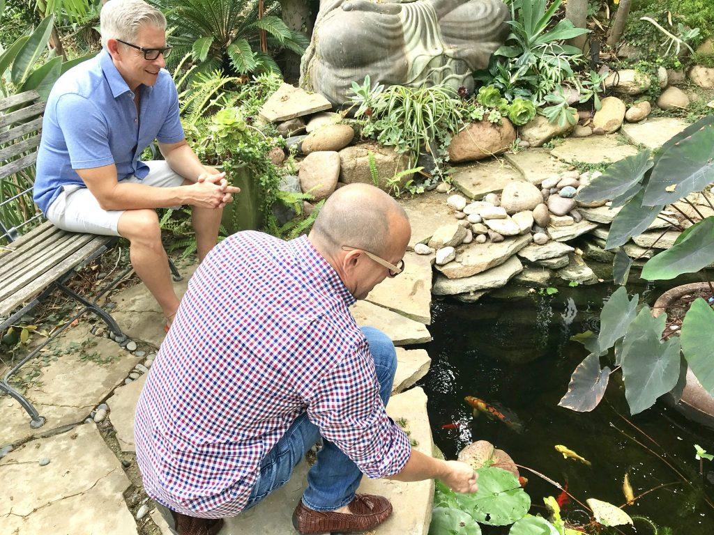 gay couple feeding koi