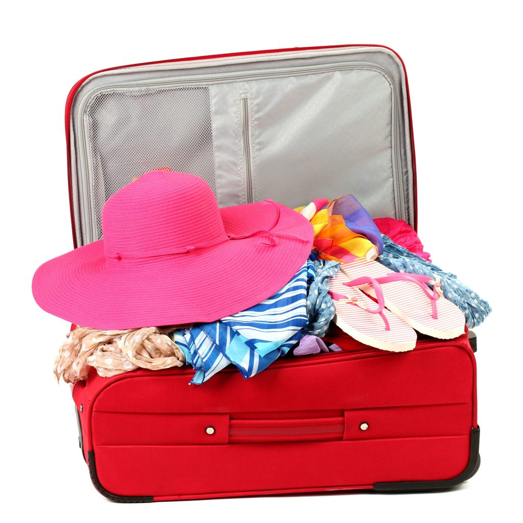 bright red luggage with women's clothing