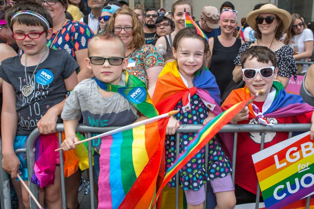kids at New York Pride March with rainbow flags