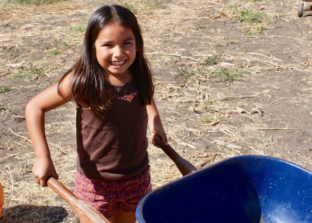 girl pushing wheelbarrow