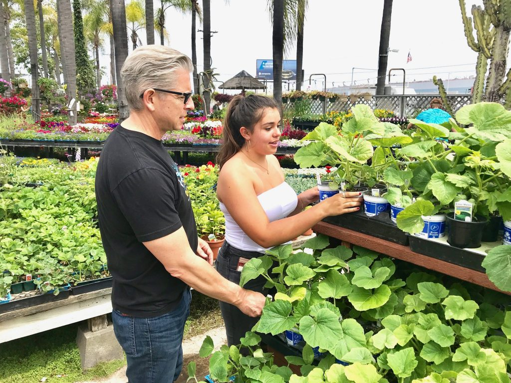 Dad and daughter picking plants at nursery