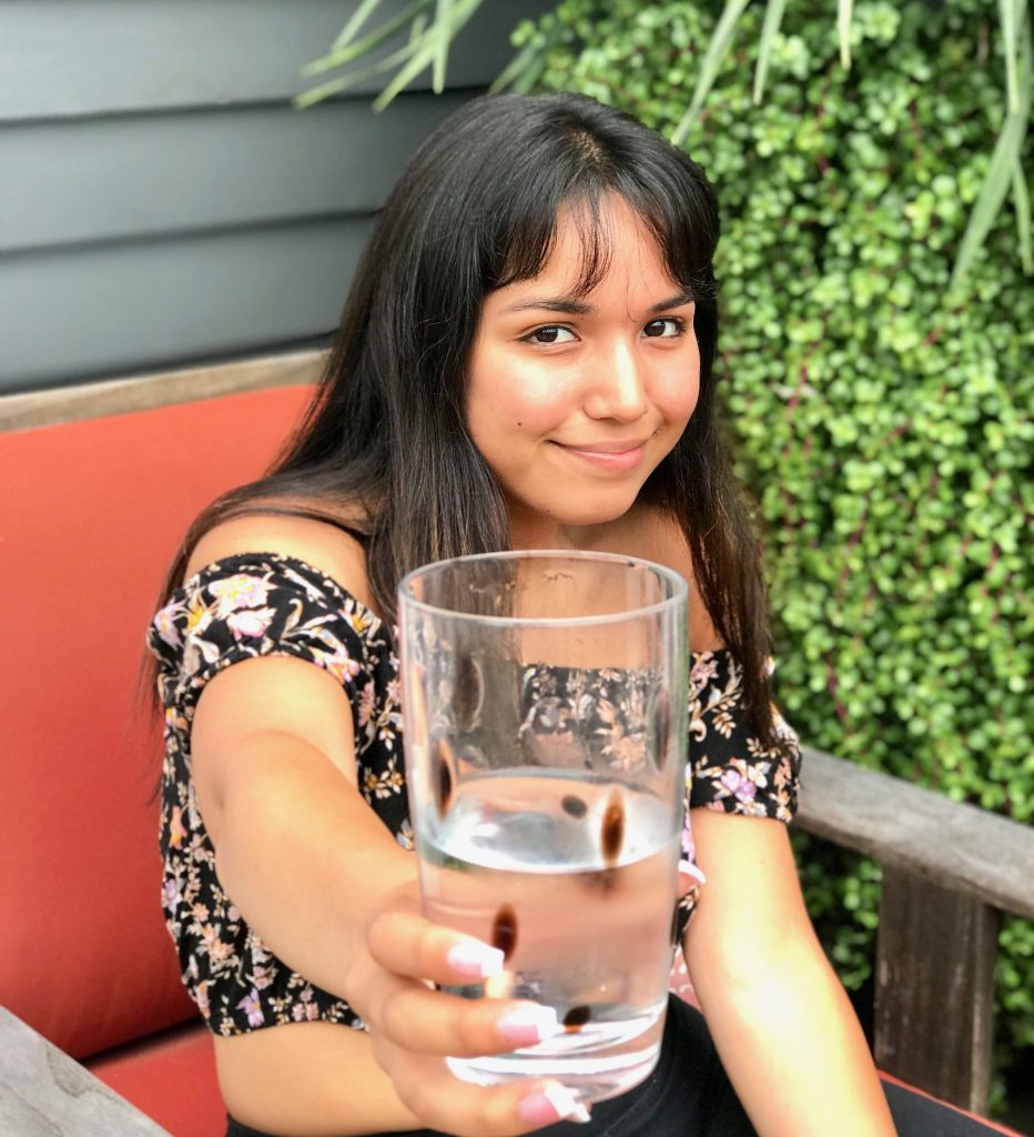 girl presenting glass of cold water