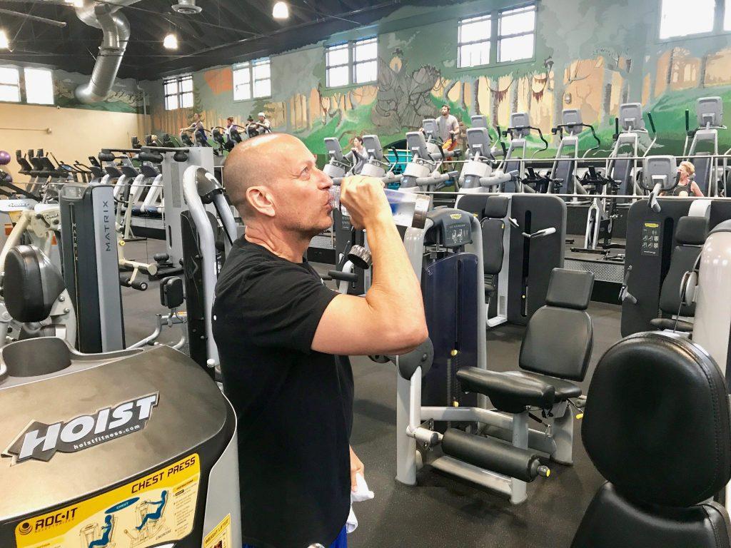 man drinking water bottle at gym