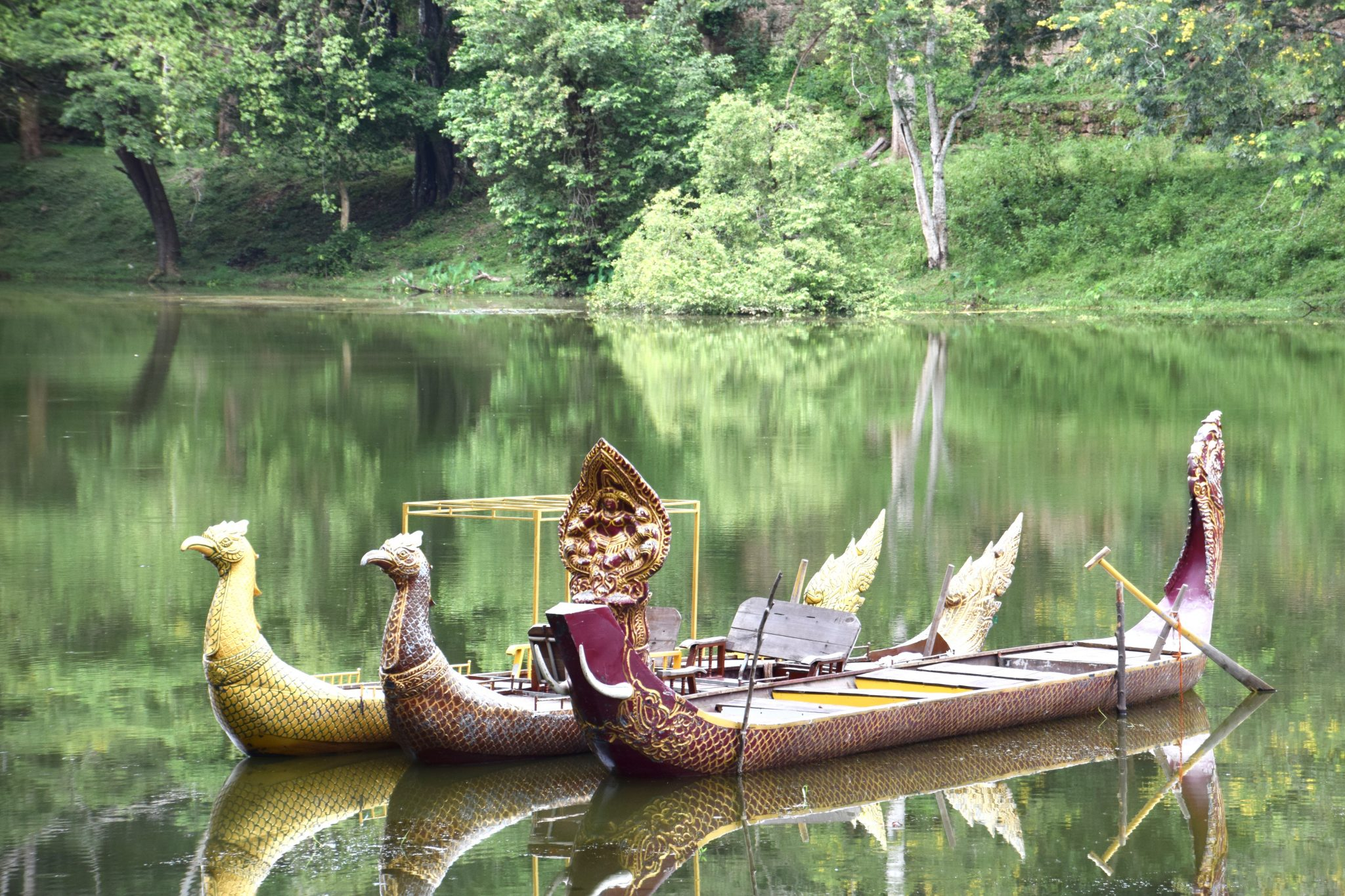 traditional Cambodian boats float on tranquil lake near Angkor Thom, Siem Reap
