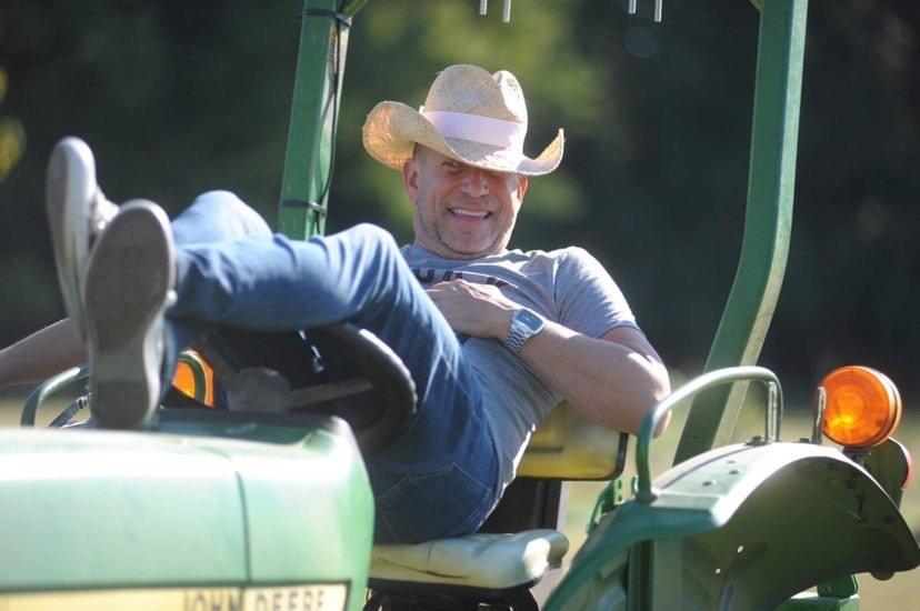 man in cowboy hat lays back in seat of John Deere tractor, Salisbury, Maryland