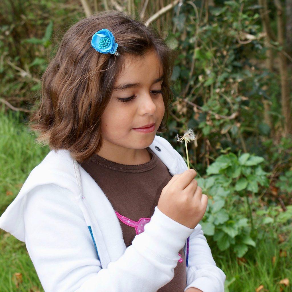 girl blowing on dandelion to make wish