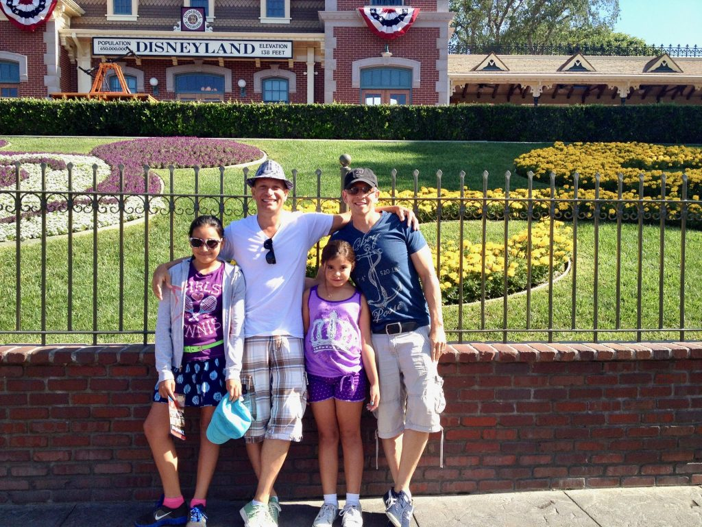 family with two dads poses with daughters at main entrance of Disneyland, Anaheim. California