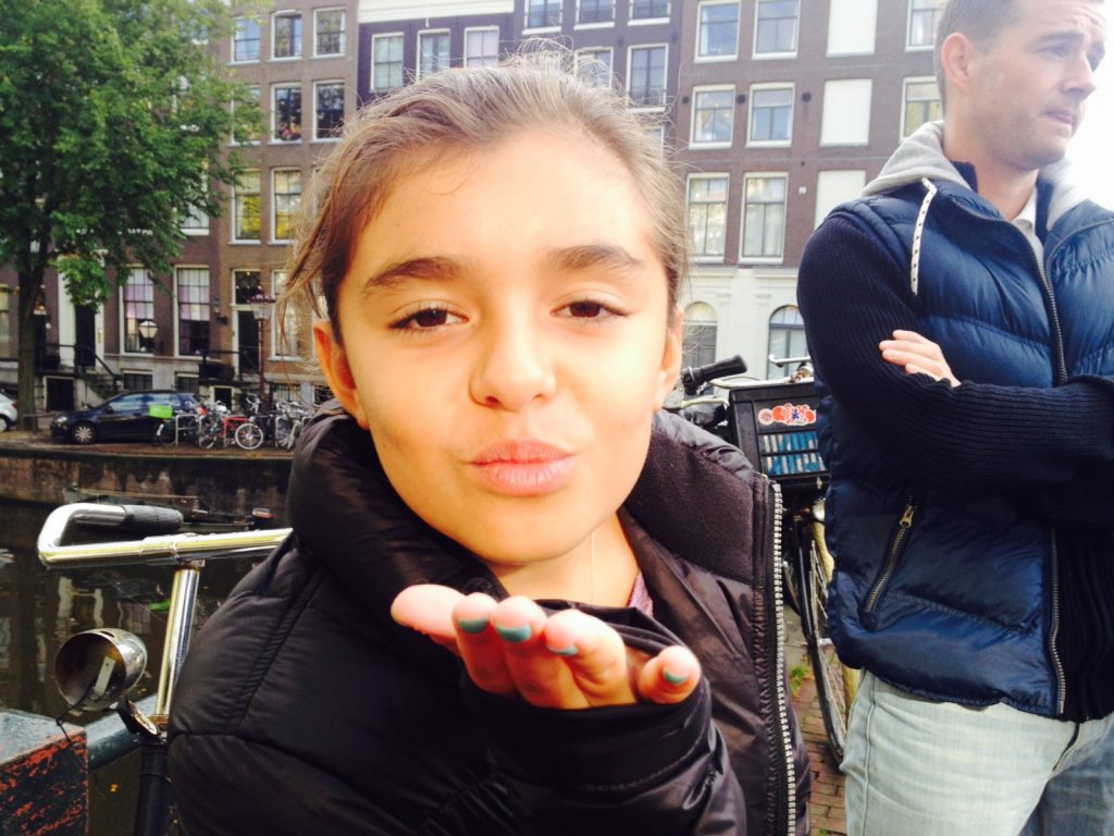girl blowing kiss on bridge in Amsterdam