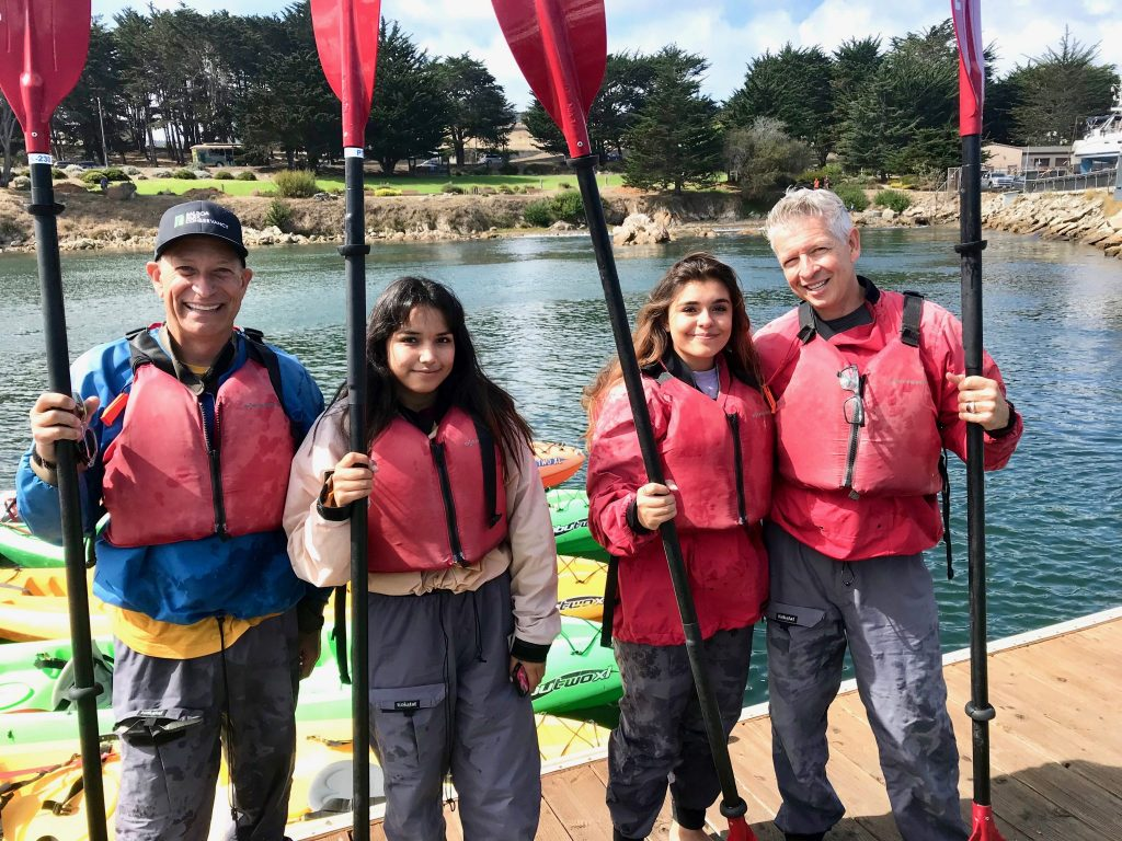 family with two dads ocean kayaking in Monterey Bay, California