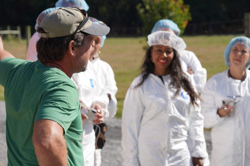 farmer explains about raising Perdue Farms organic chickens to visiting media