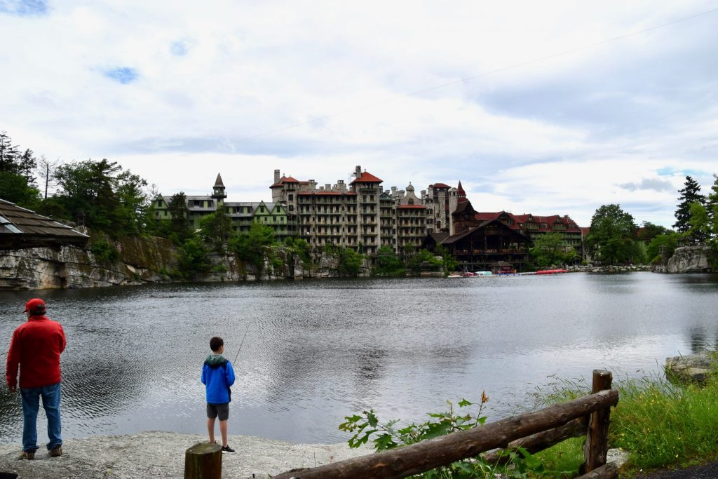 boy and dad fishing at Mohonk Lake with Mohonk Mountain House in distance, New York
