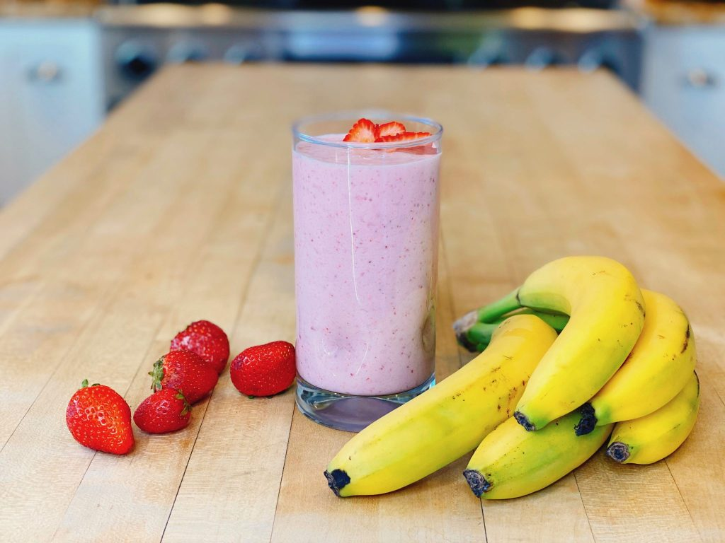Strawberry Banana smoothie with fresh fruit on wood counter