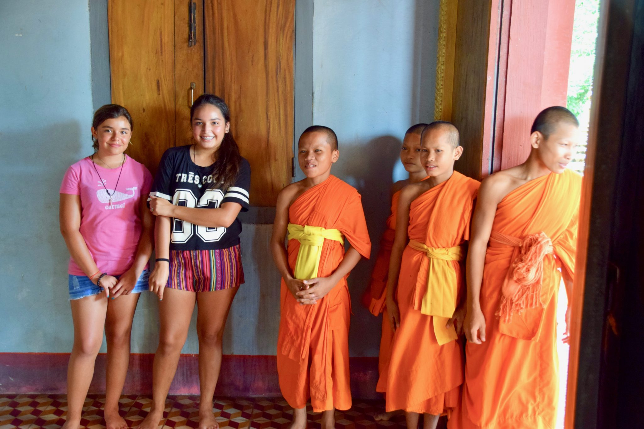 American girls pose with boys in training to become Buddhist Monks in Siem Reap, Cambodia