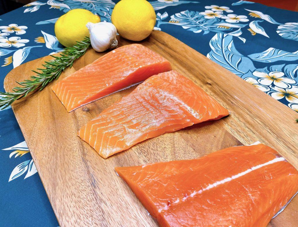 raw salmon steaks on wood serving board