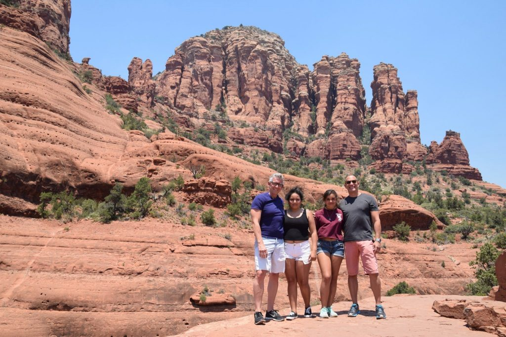 Family with two dads on colorful rock formations in Sedona, Arizona