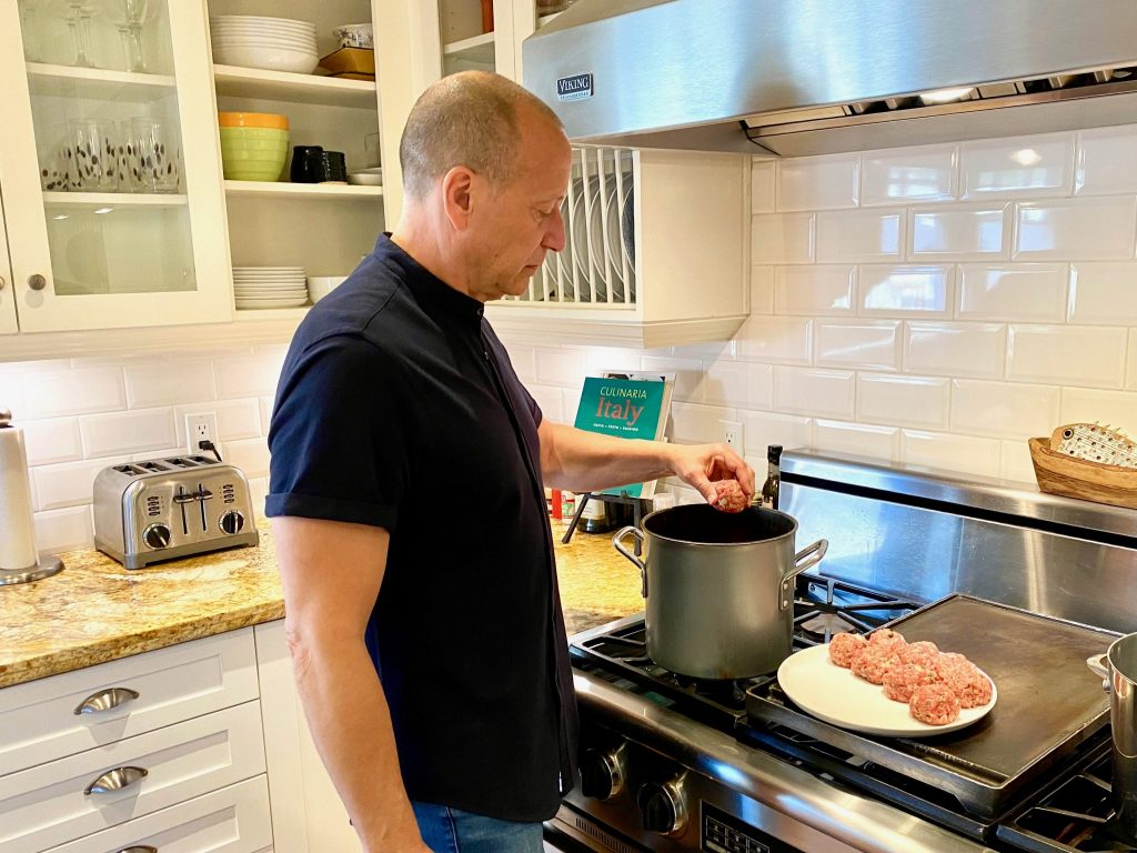 man in kitchen putting meatballs into pasta sauce to cook over stove