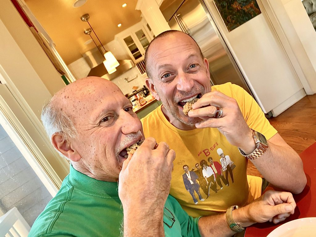 older brothers eating cookies in kitchen