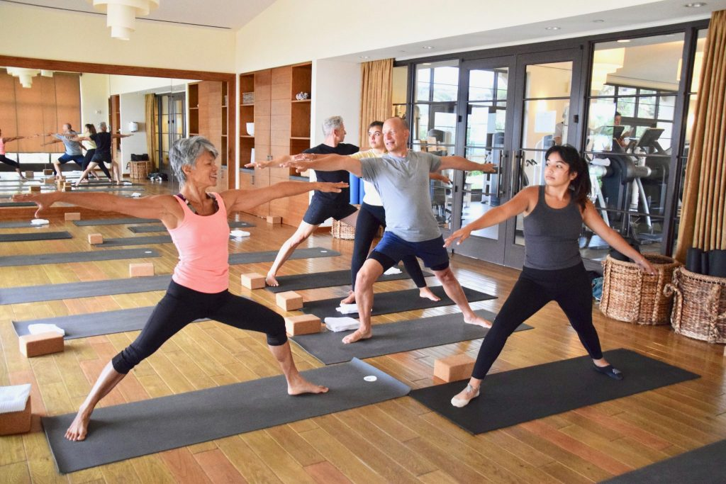 family taking private yoga class in mirrored yoga studio with instructor