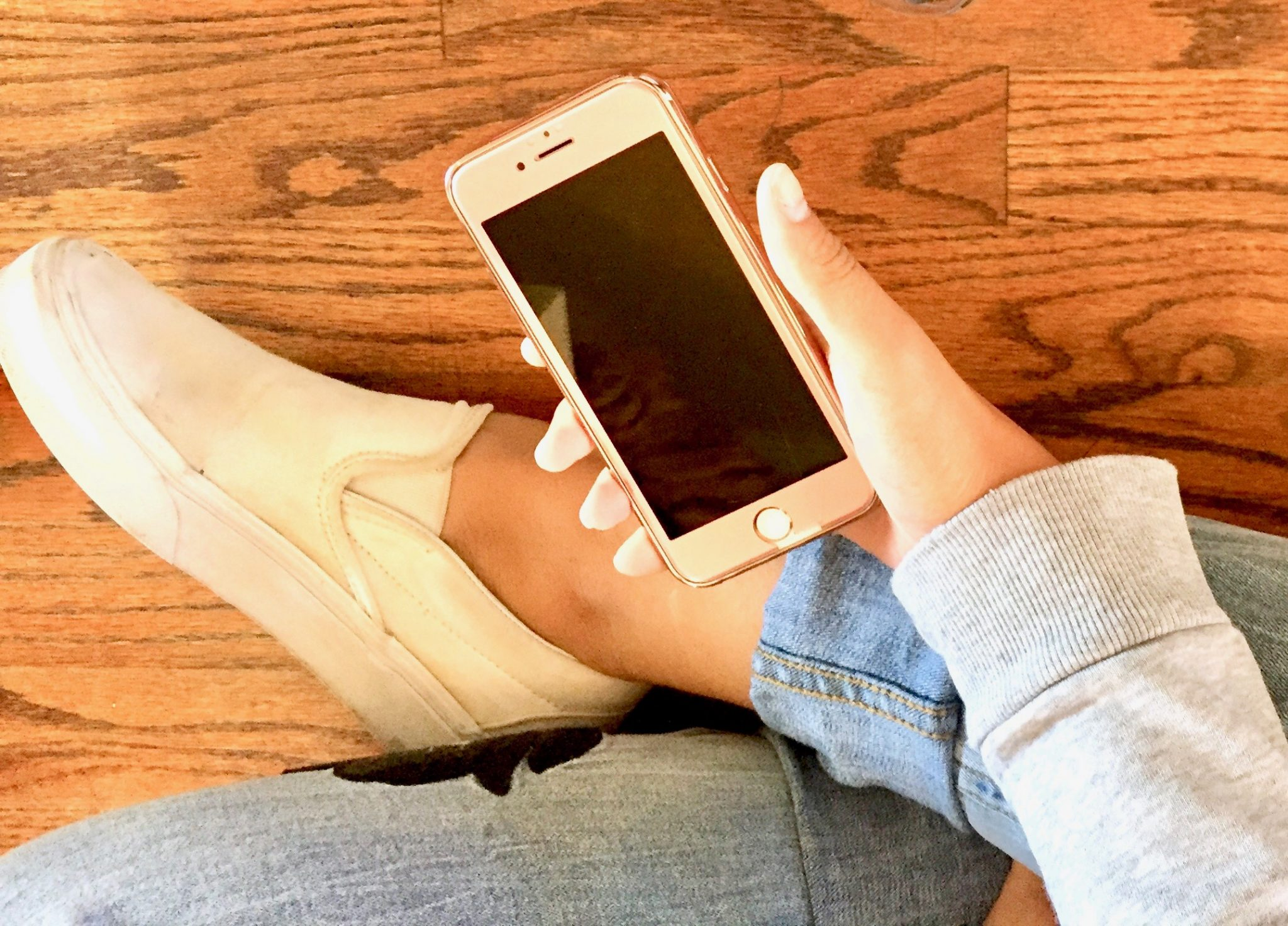 iPhone in girl's hand while sitting on a hardwood floor