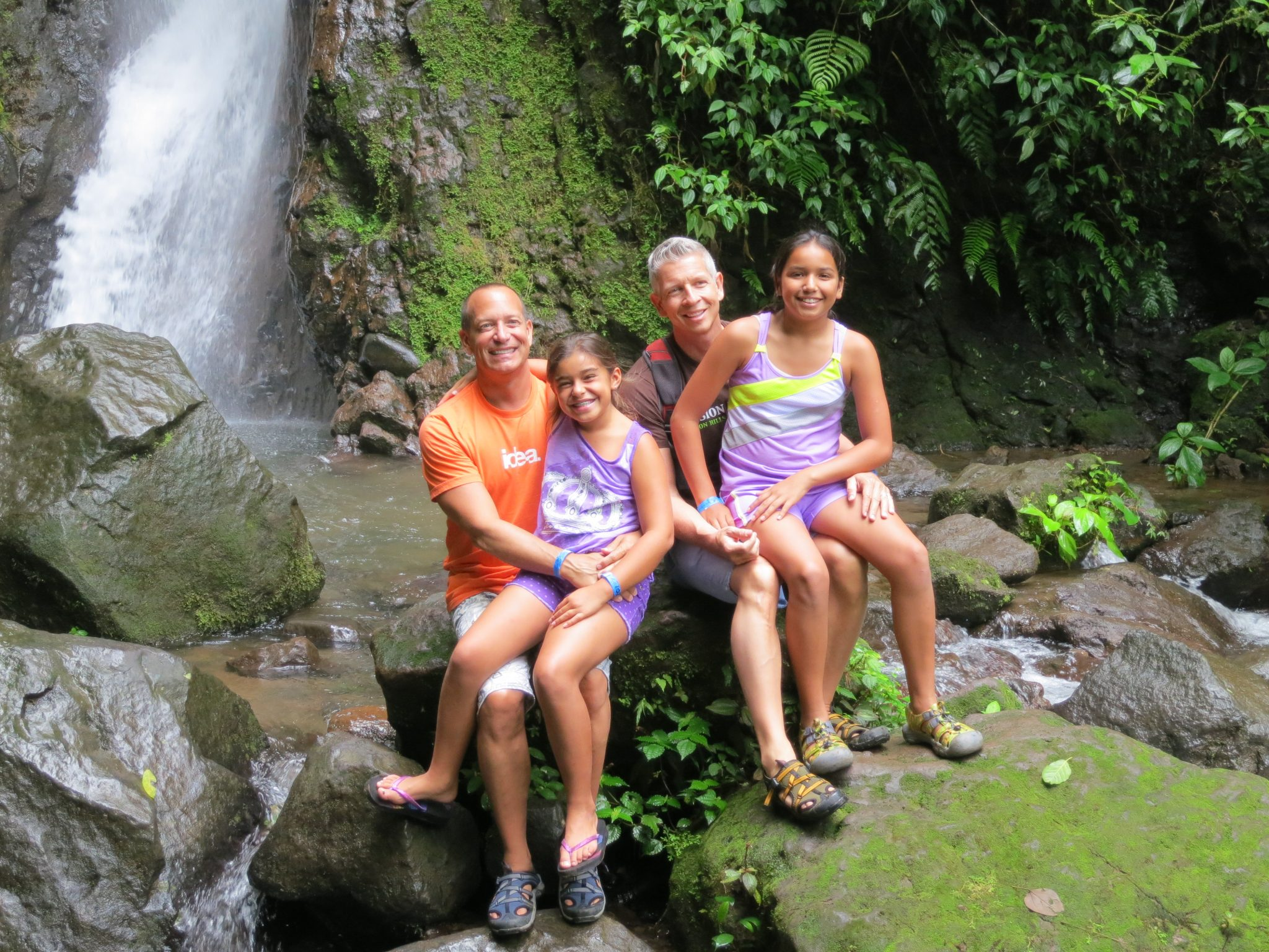 family with two dads at jungle waterfall in Costa Rica