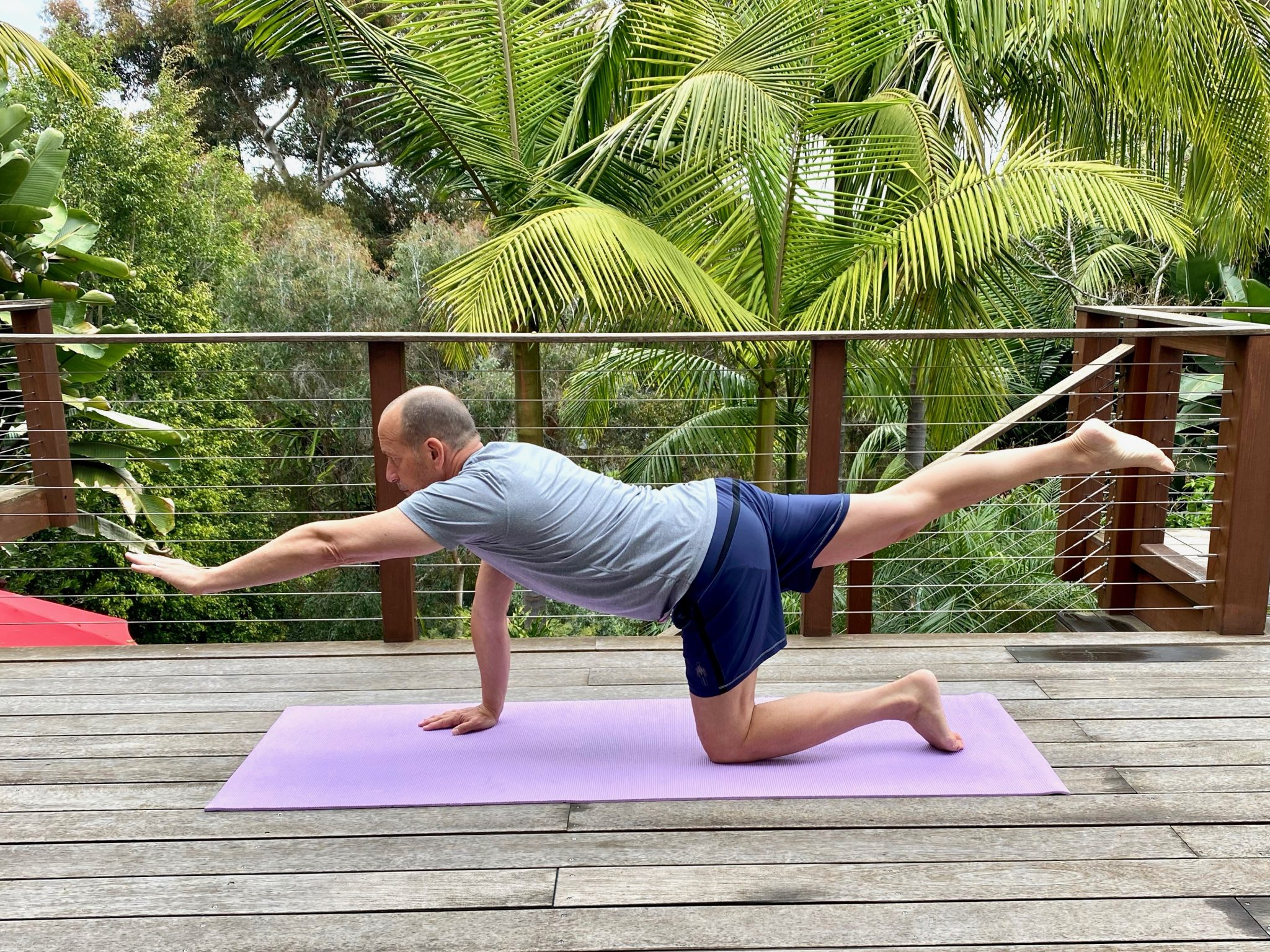 Man doing yoga on deck with tropical setting