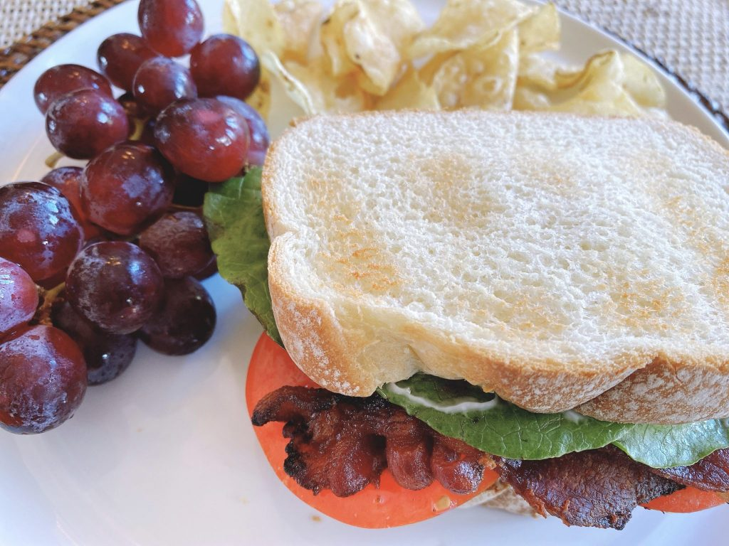 Bacon lettuce and tomato sandwich with grapes and potato chips