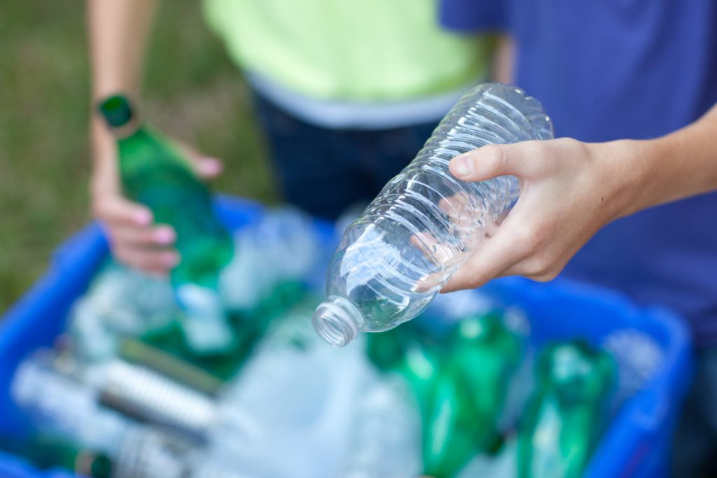 Boy and girl putting clear and green bottles and metal cans in recycling blue bin outside in yard