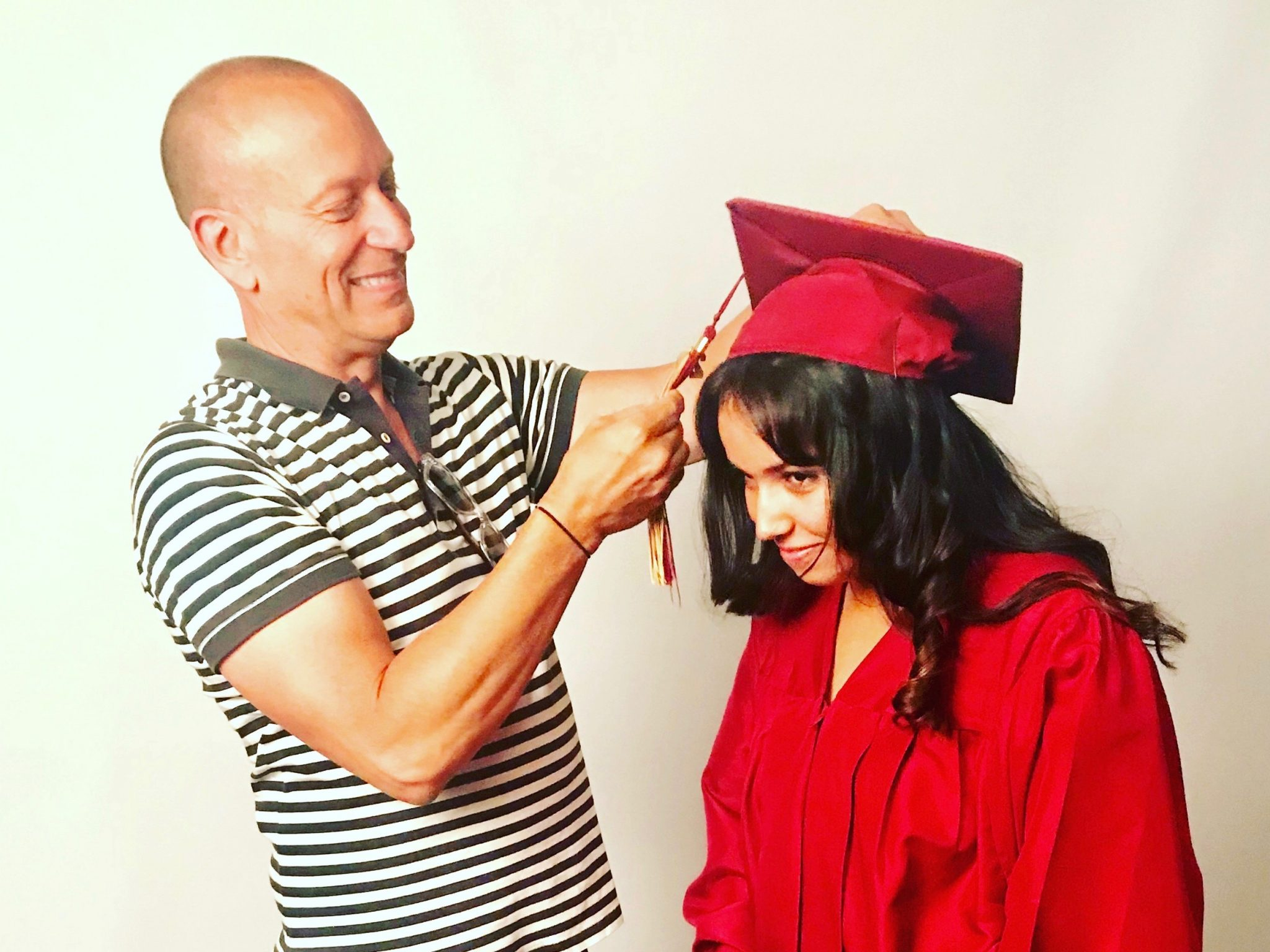 man helps daughter with graduation cap and robe