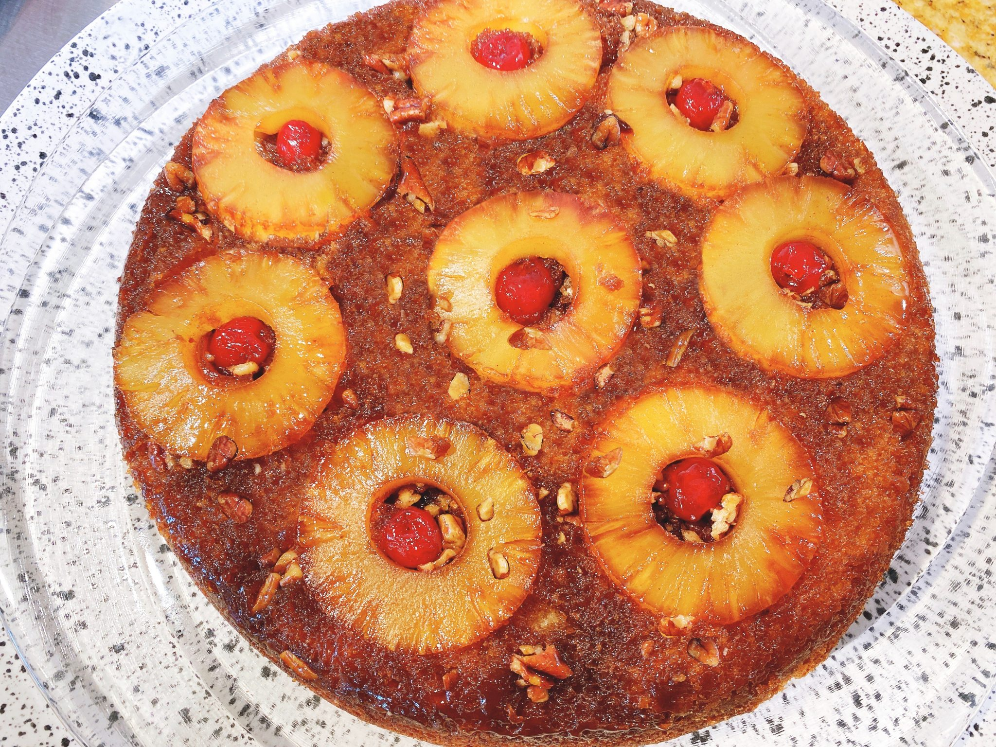 whole pineapple upside down cake with pineapple rings, pecans, brown sugar caramel and maraschino cherries