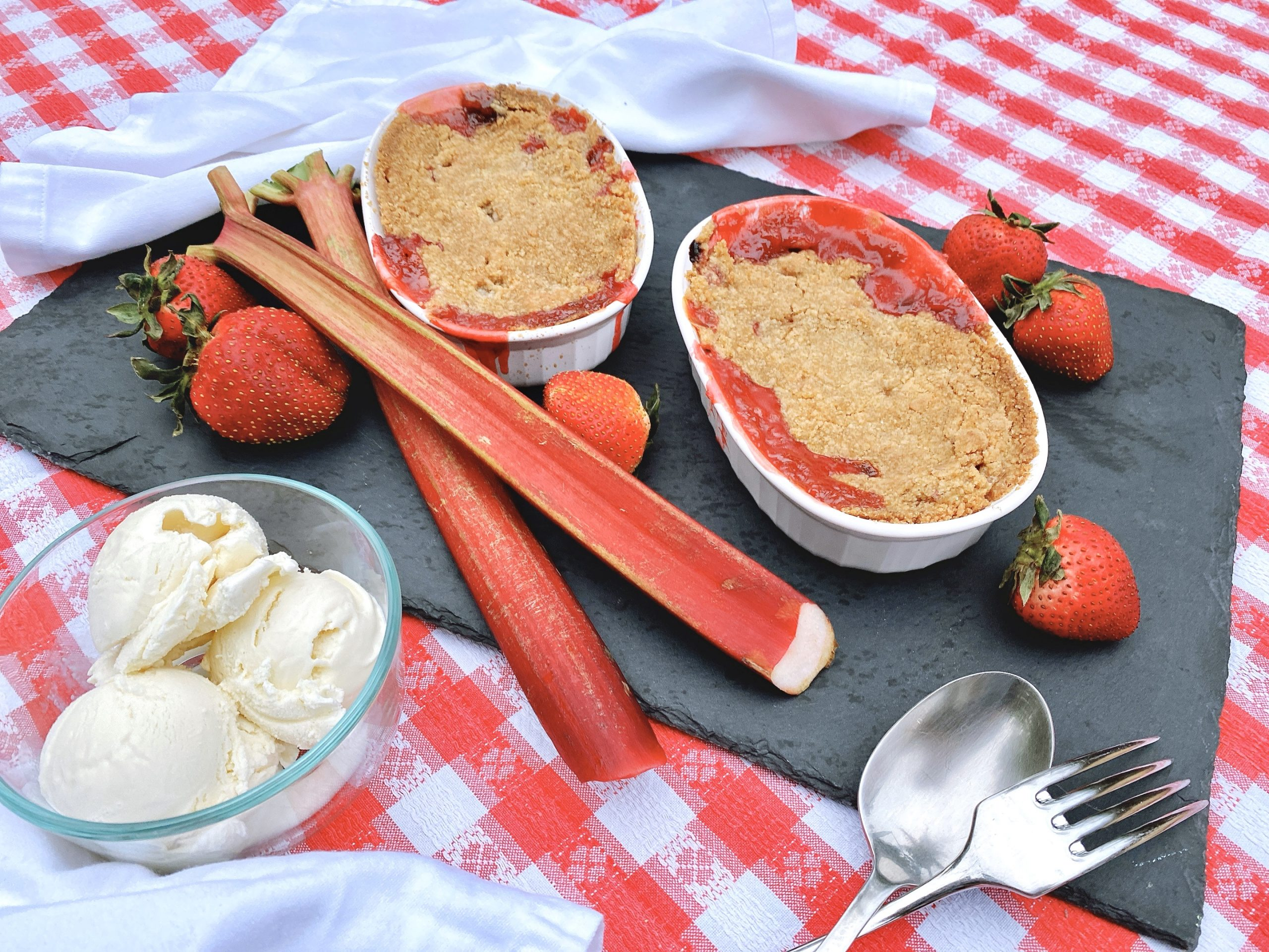 strawberry rhubarb crisp baked in oval ramekins and ready to serve