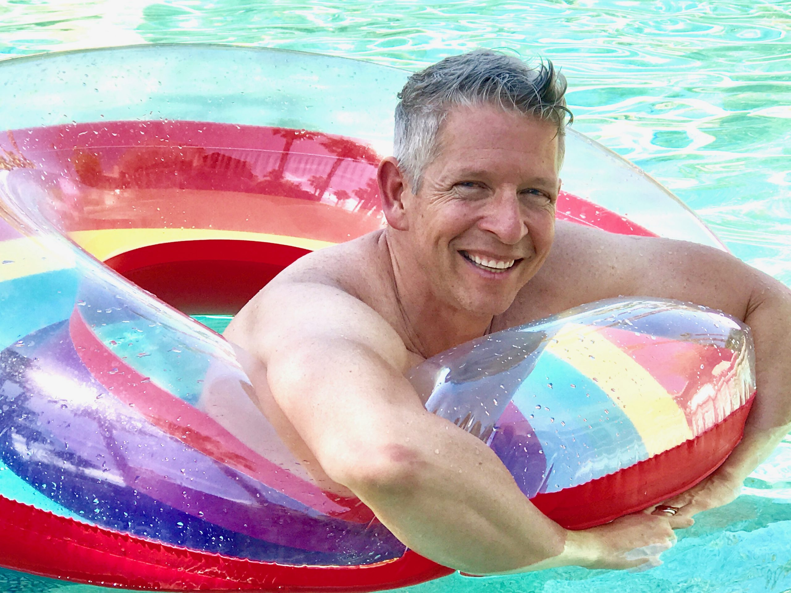Smiling grey haired man floating in colorful rainbow pool toy