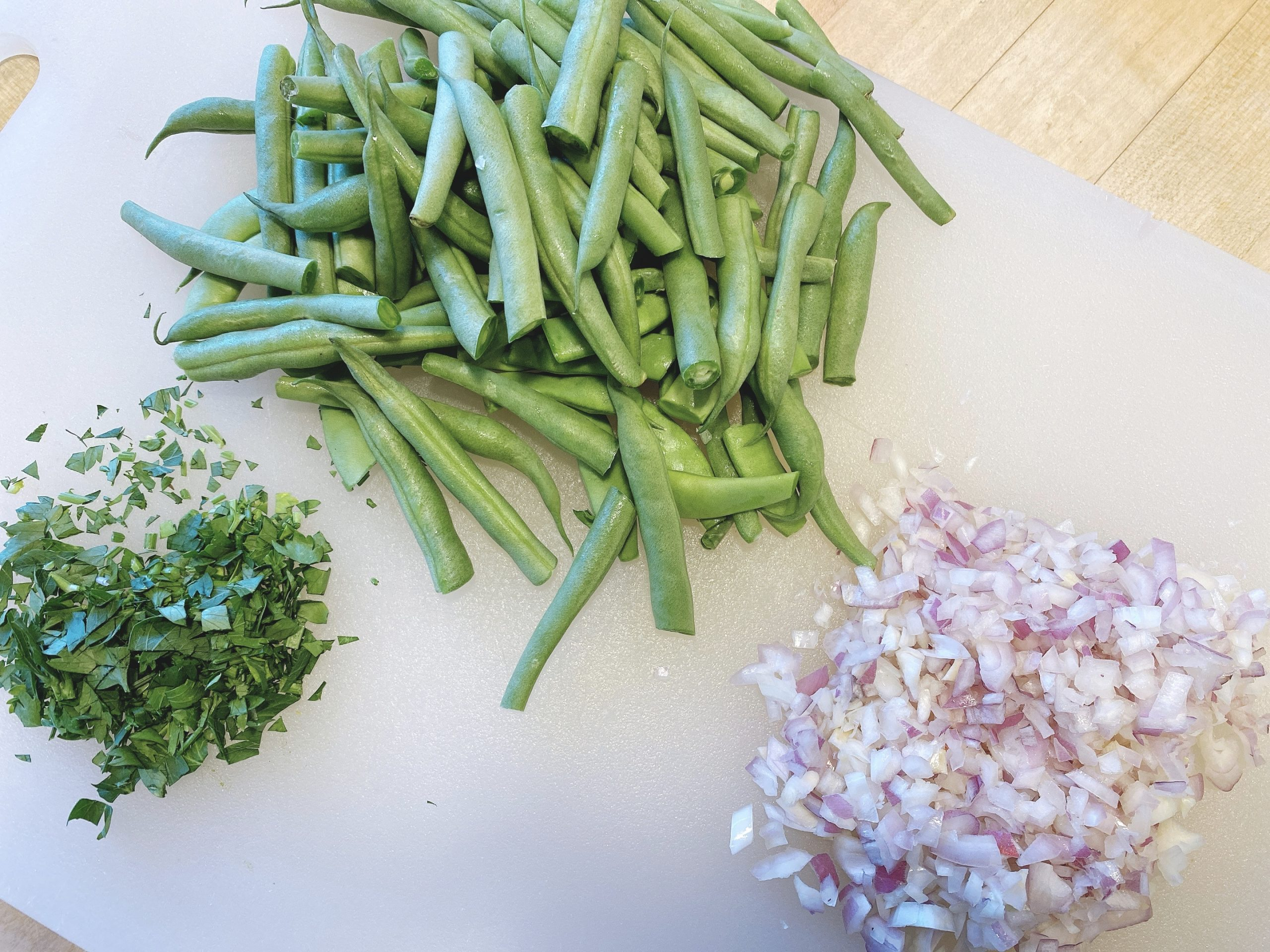 Ingredients for pasta with green beans including chopped onions and parsley