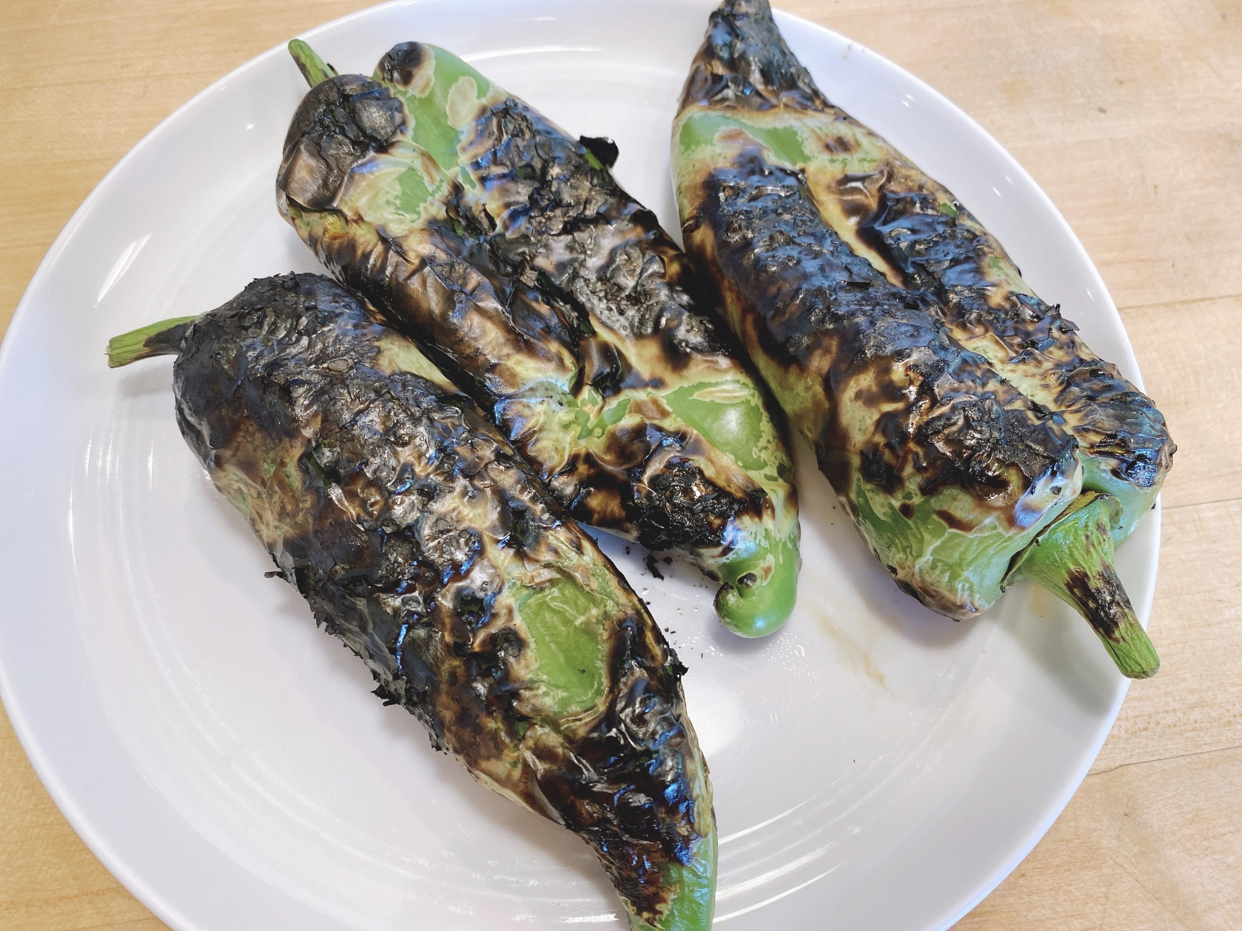 Charred anaheim chilis on a white plate