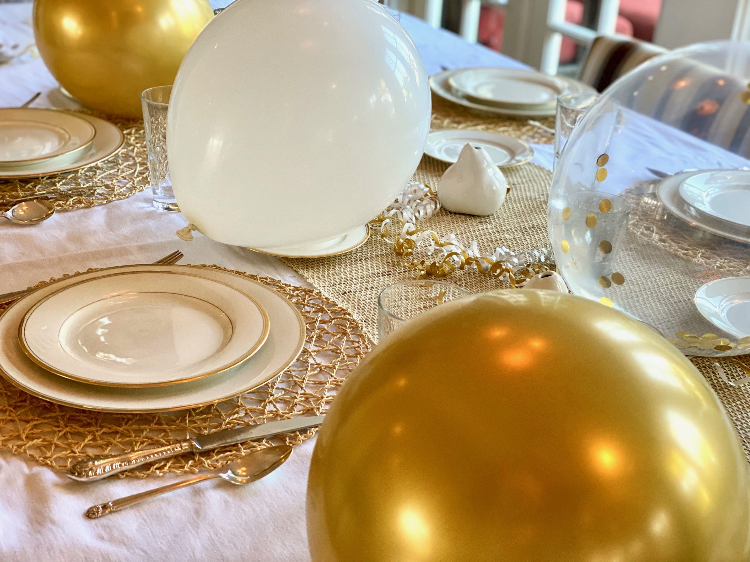 Golden and white table setting for festive dinner party