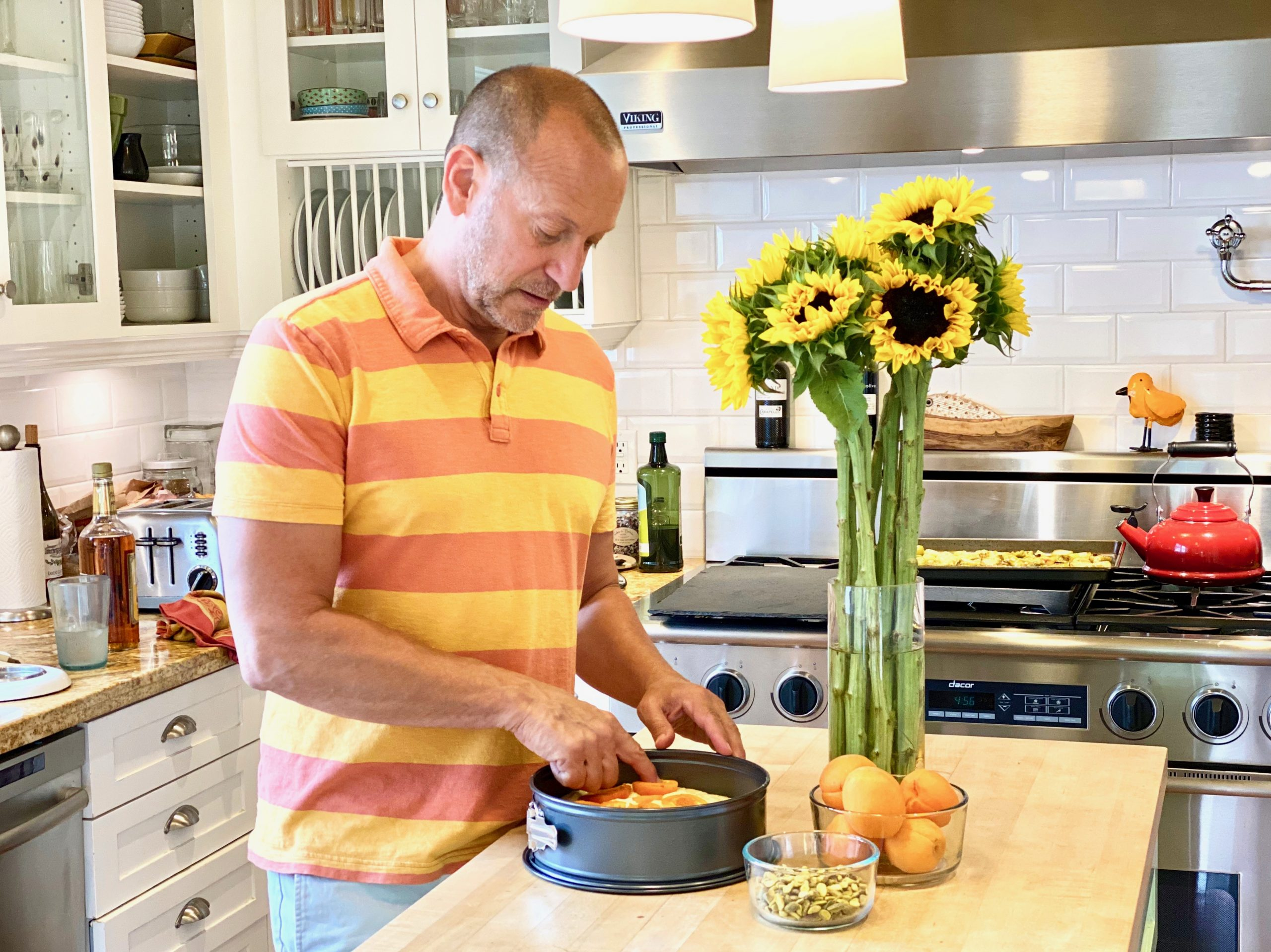man in white kitchen placing fresh apricots on top of cake before baking