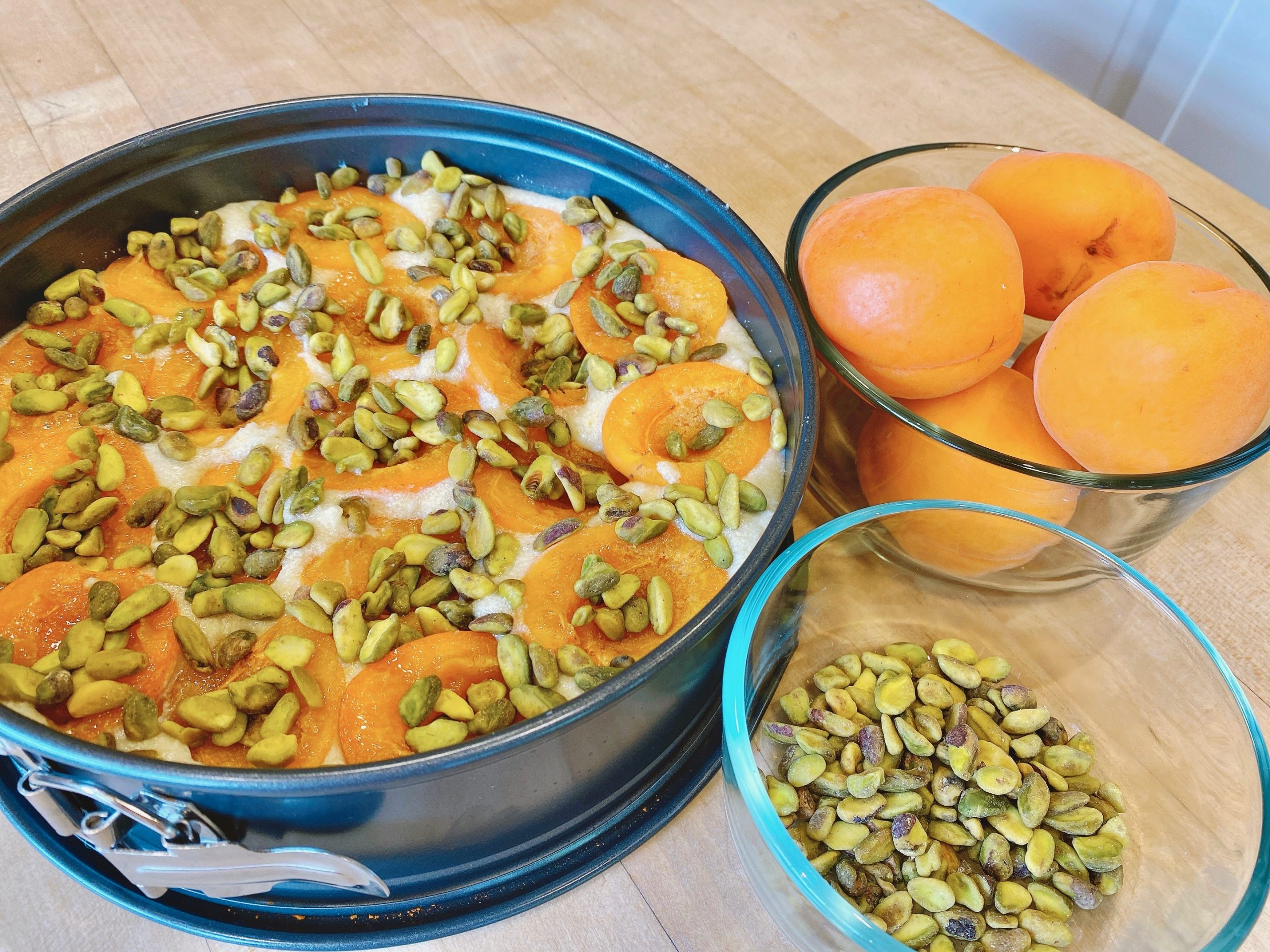 Uncooked Apricot Pistachio Cake with a side bowl of whole fresh apricots and roasted pistachio nuts