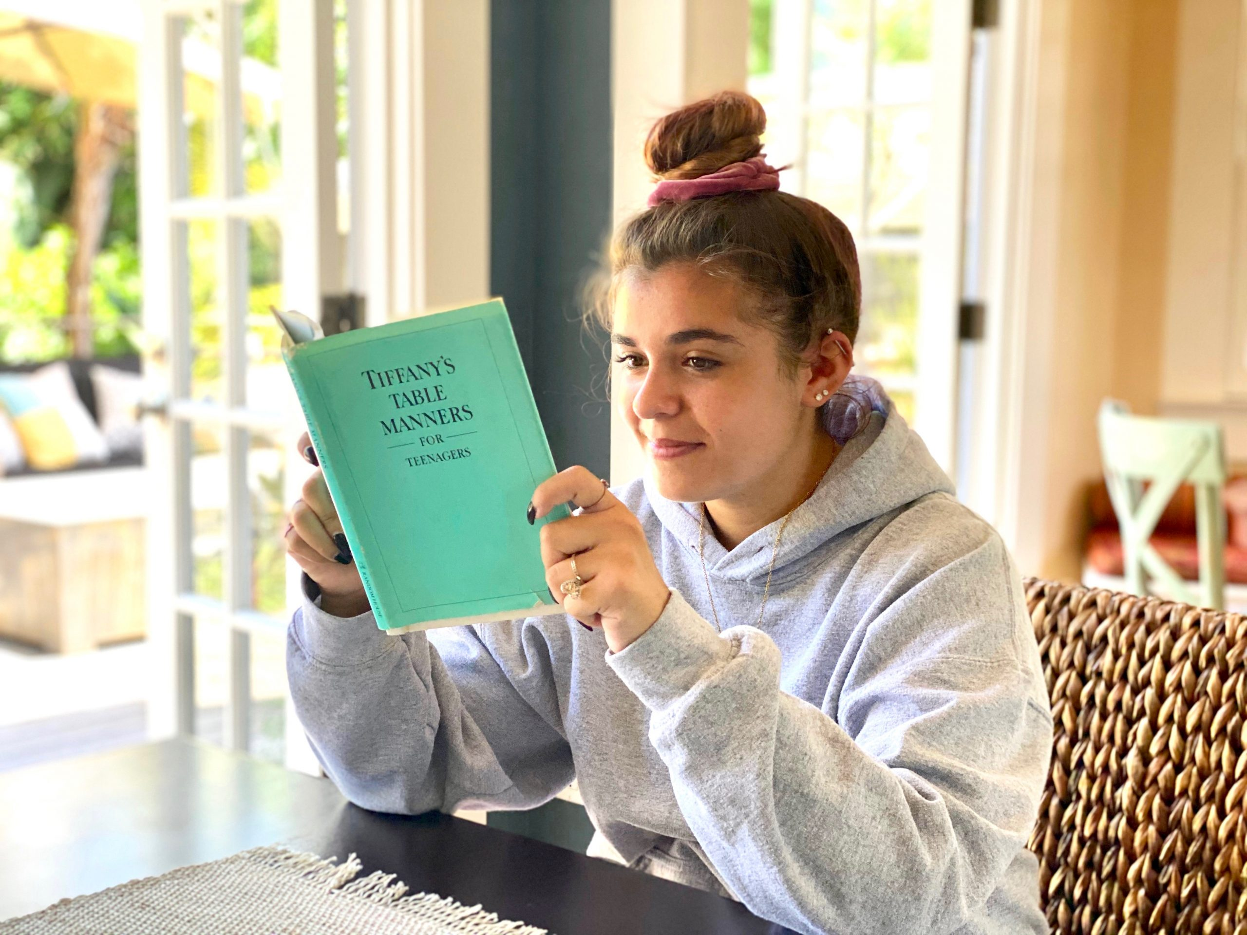 Girl reads Tiffany's Table Manners for Teenagers while sitting at dining room table at home