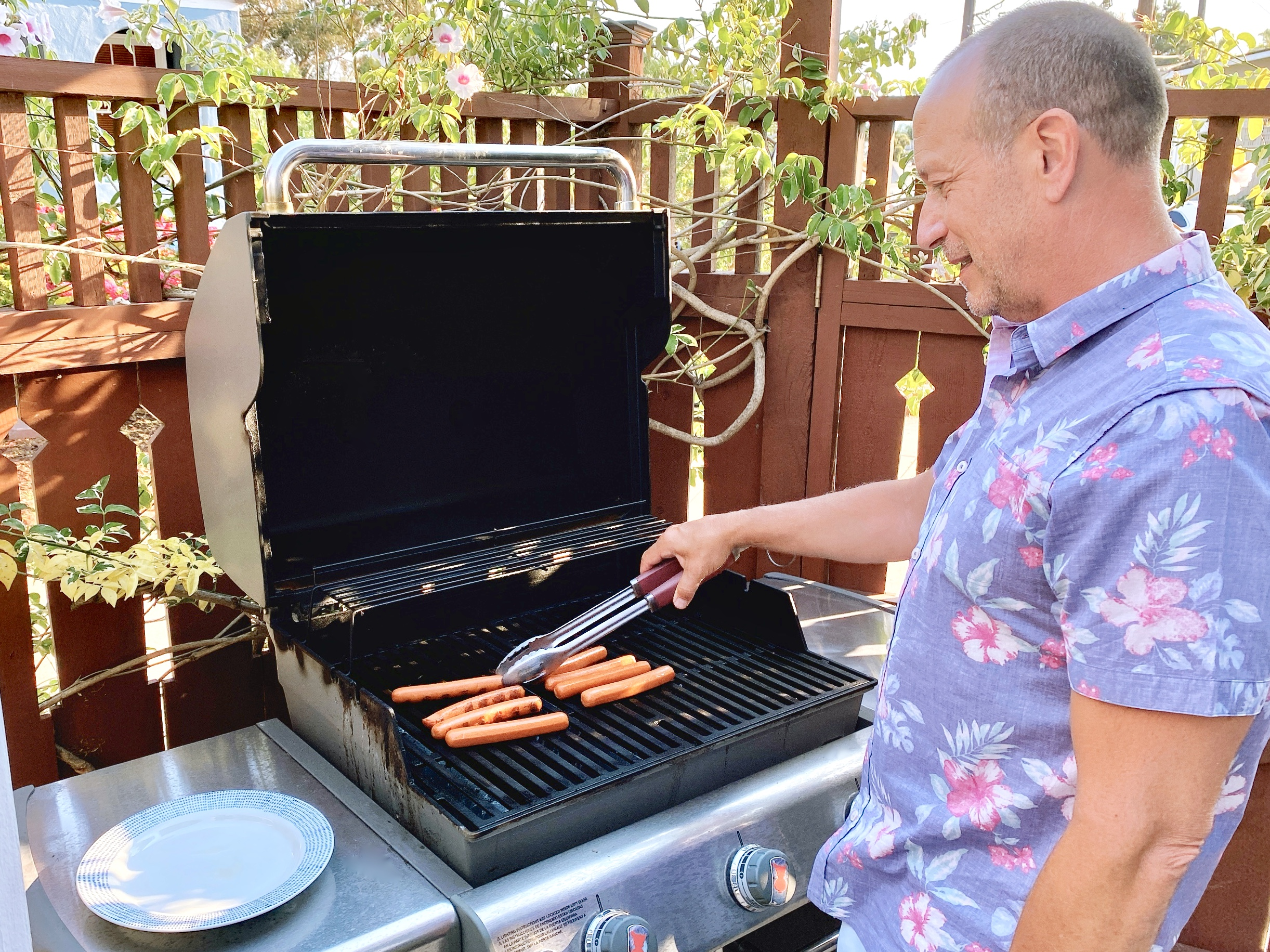 man grilling hot dogs on patio BBQ