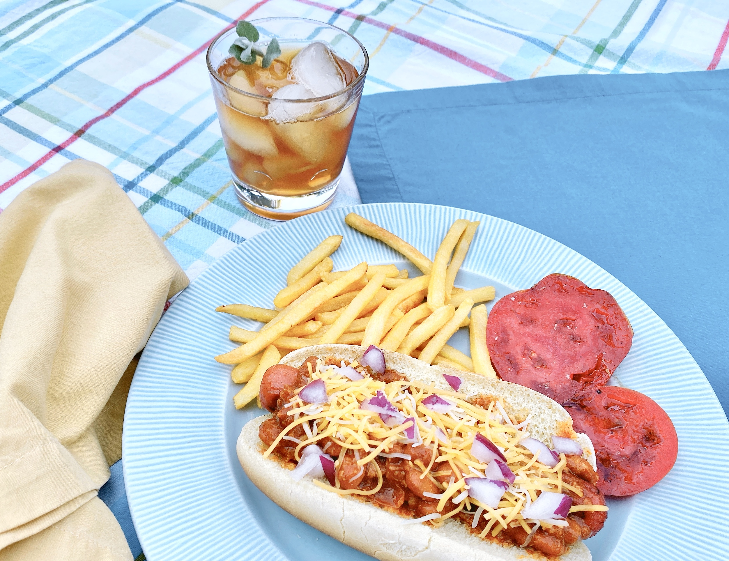 chili dog and fries served picnic style with colorful plaid tablecloth and iced tea