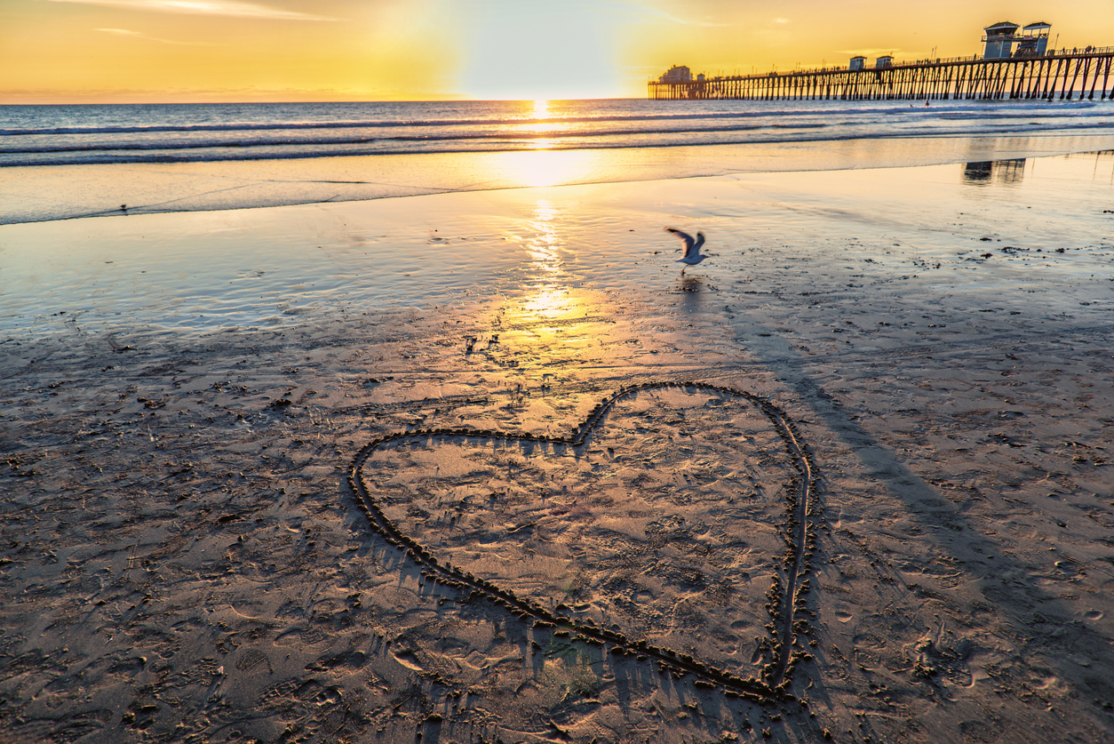 A valentine drawn into the sand at the Oceanside Pier, located in northern San Diego County about 30 miles north of the city of San Diego, shot at sunset.