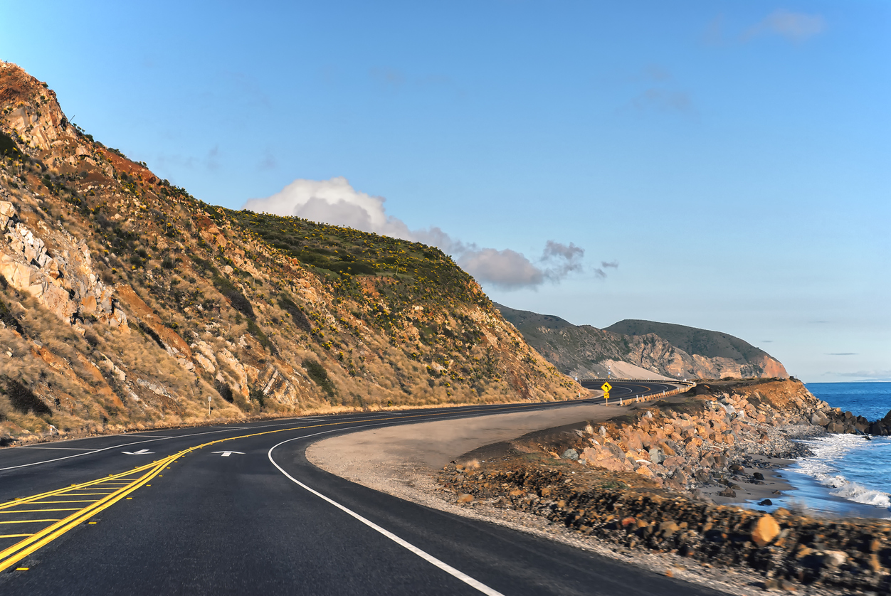 Serene view of empty Pacific Coast Highway running parallel to the California coastline