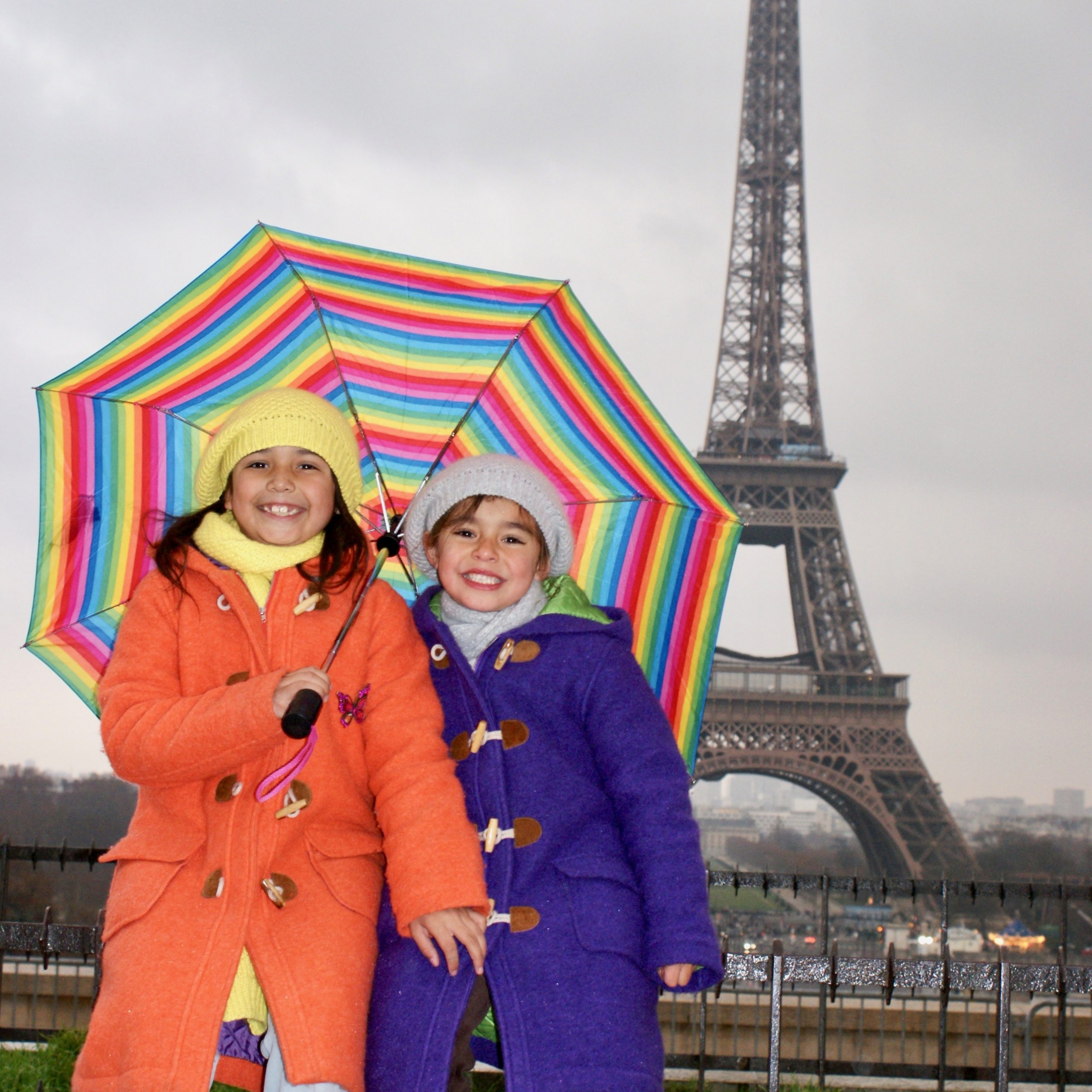Two young girls hold a rainbow umbrella with the Eiffel Tower in the background, Paris, France
