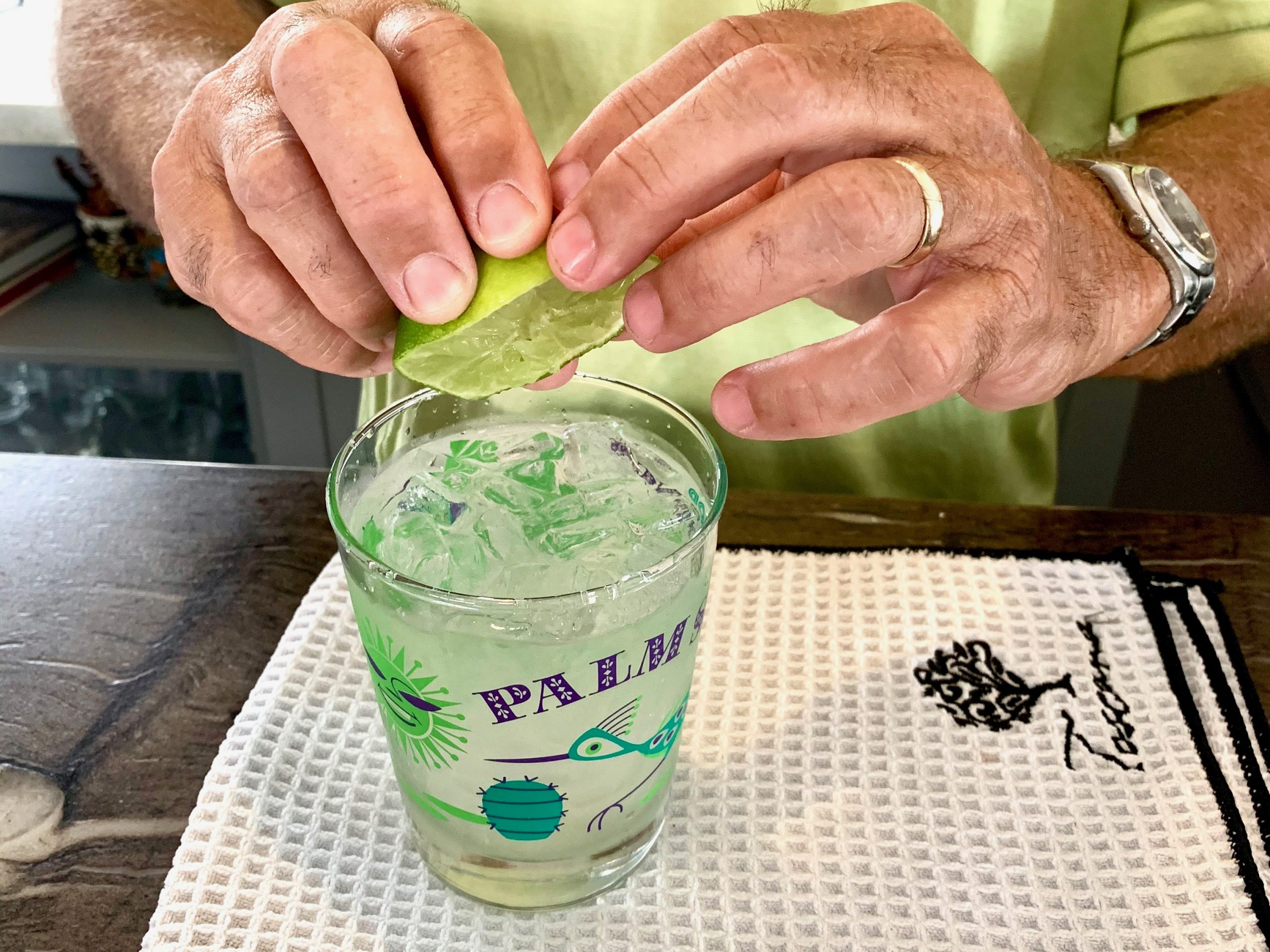 Freshly made margarita with man squeezing lime