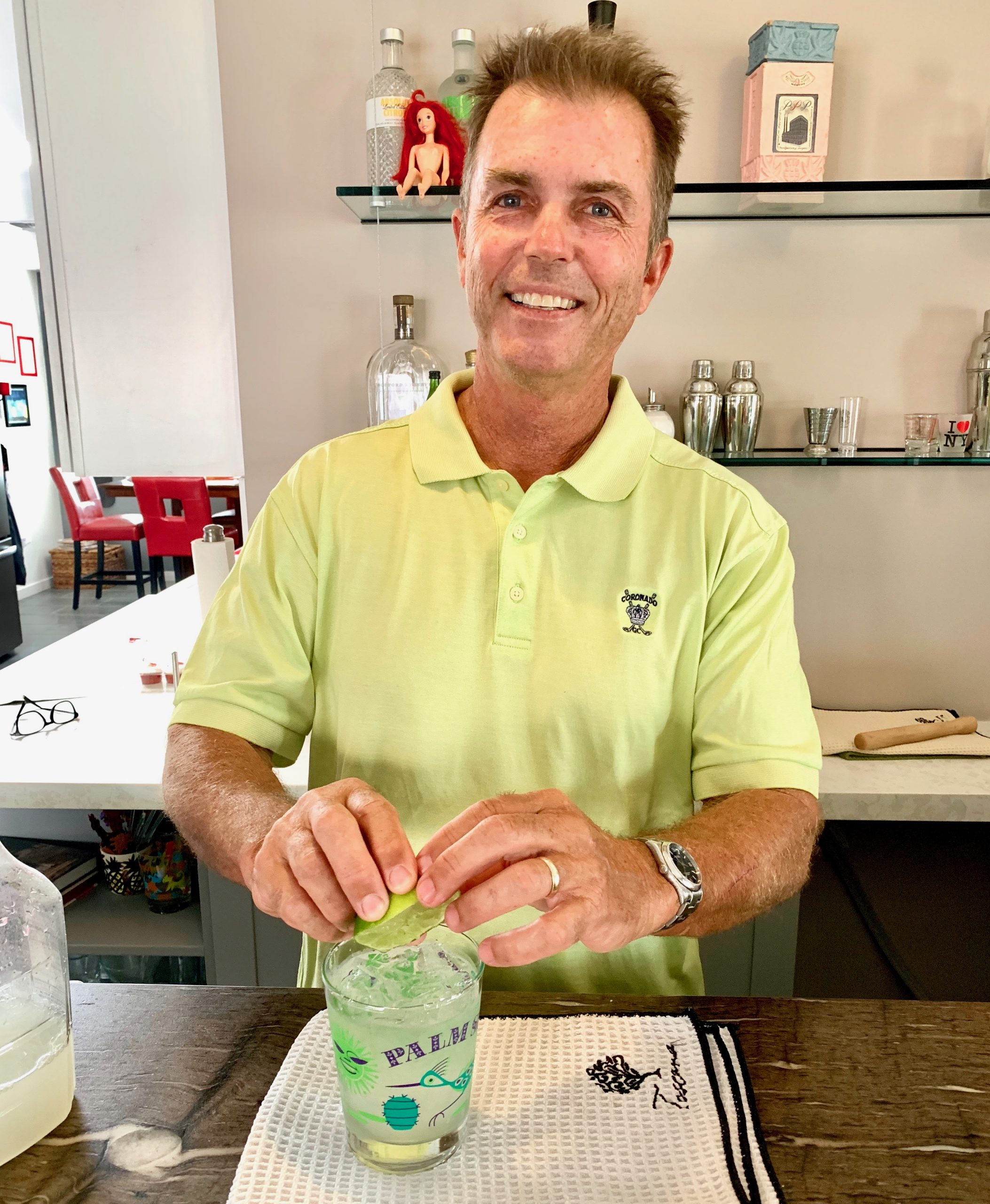 Man at his home bar smiling at camera as he squeezes a fresh lime into his freshly made margarita