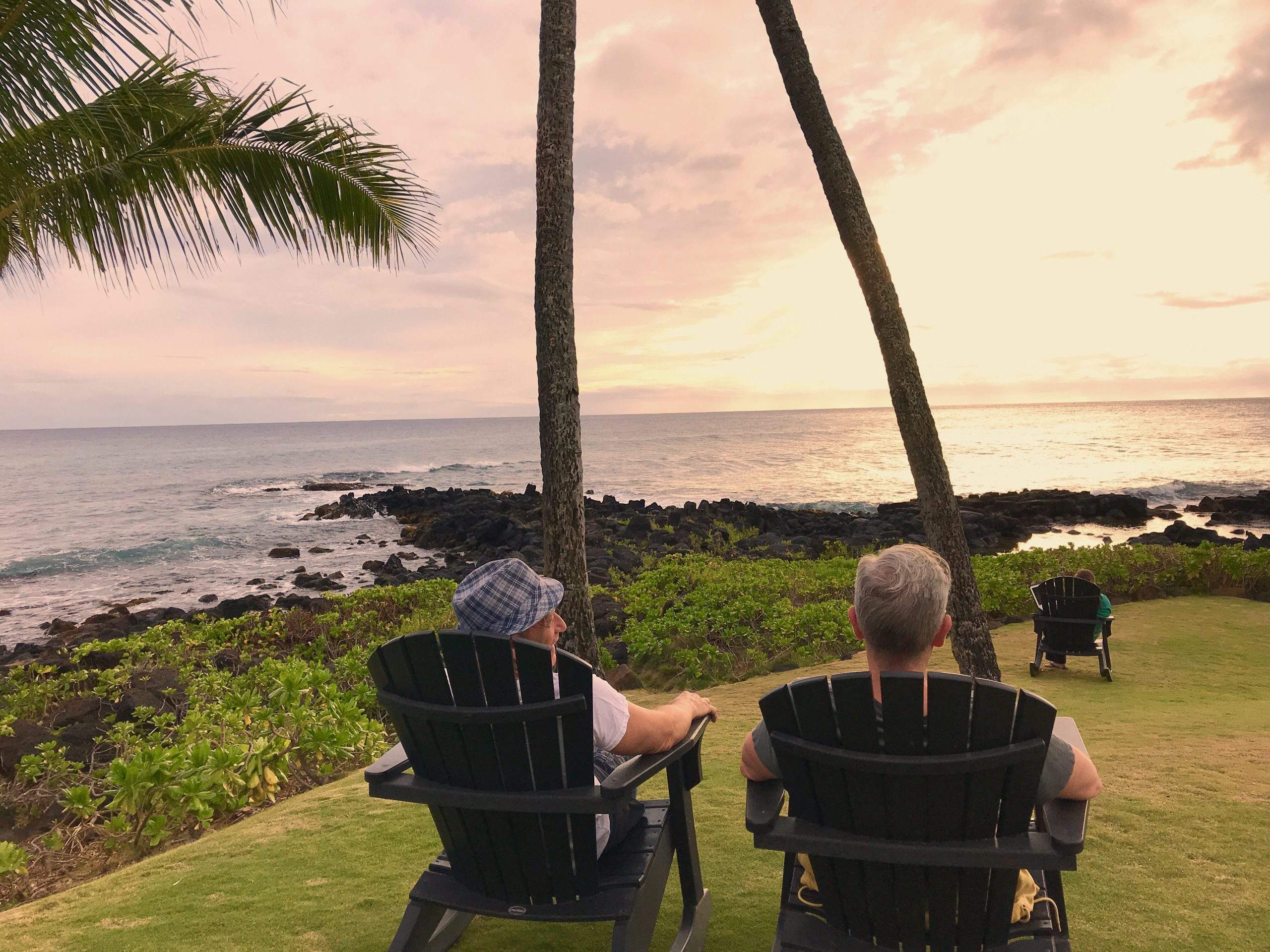 Gay male couple enjoys the sunset in lounge chairs overlooking the ocean in Poipu, Kauai, Hawaii