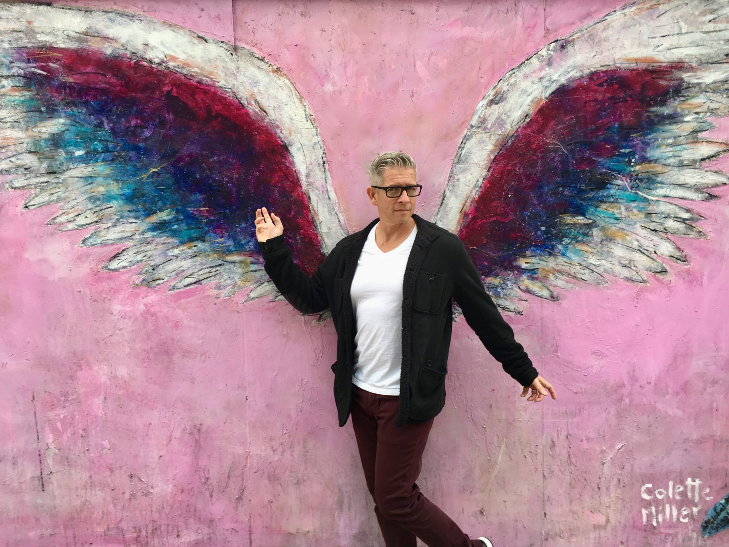 Man poses in front of famous angel wings mural on Melrose Avenue in Los Angeles, California