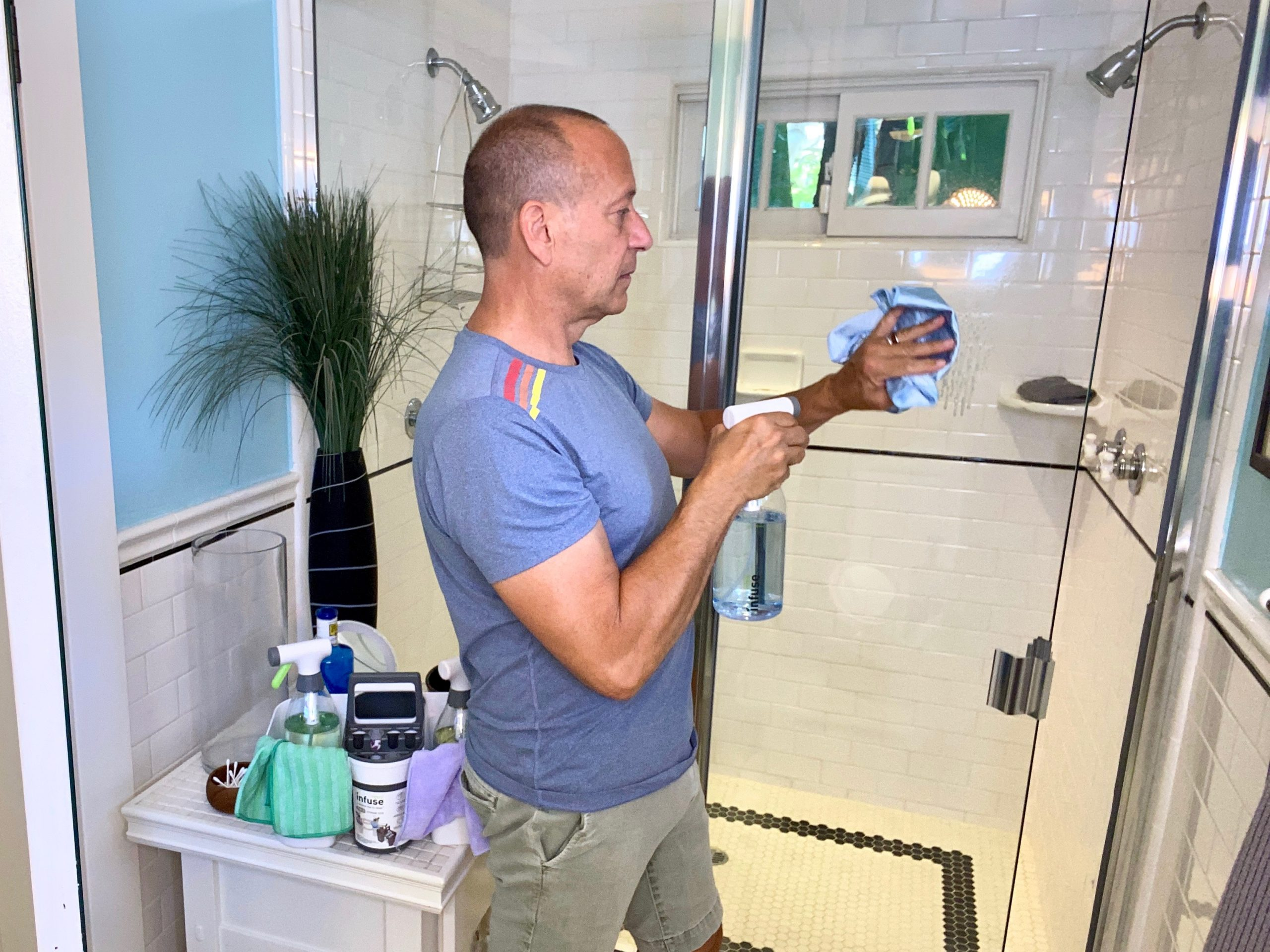 man cleans glass shower door with Infuse Cleaning System spray bottle and cloth