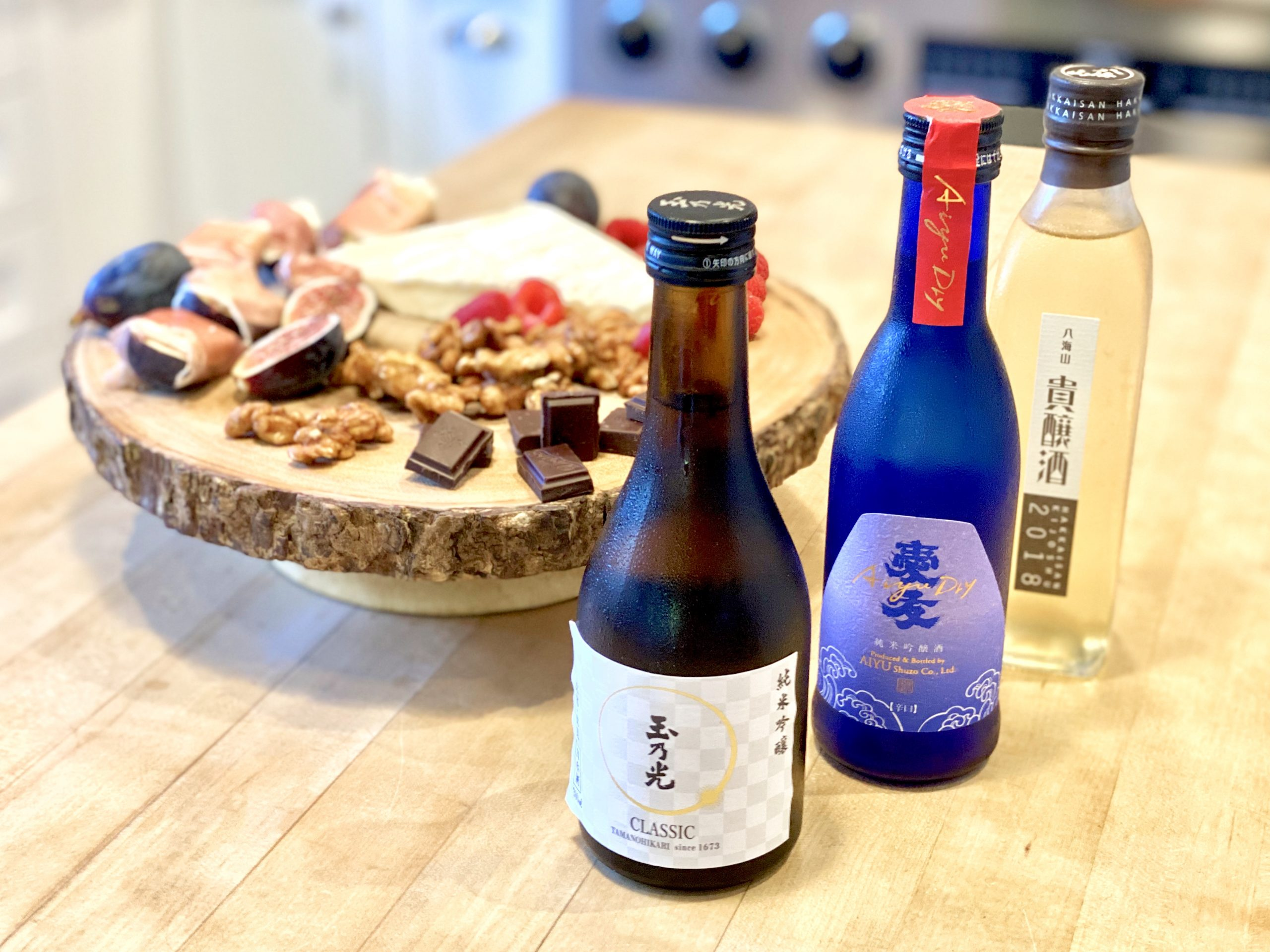 three bottles of sake from different areas of Japan, served cold with food pairing of cheeses, nuts, berries and chocolate