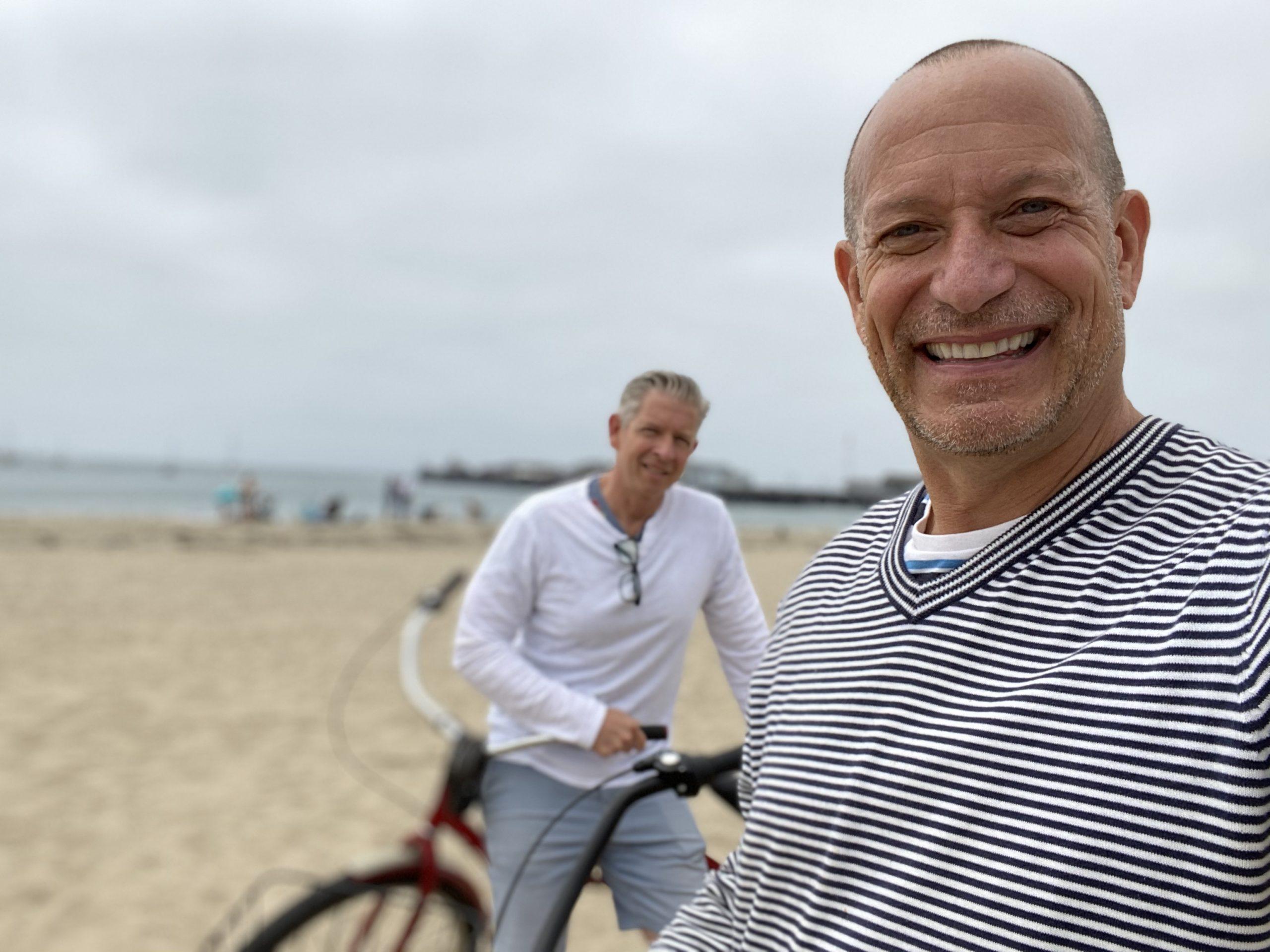 two men stop for photo while riding bikes along beachfront in downtown Santa Barbara, CA