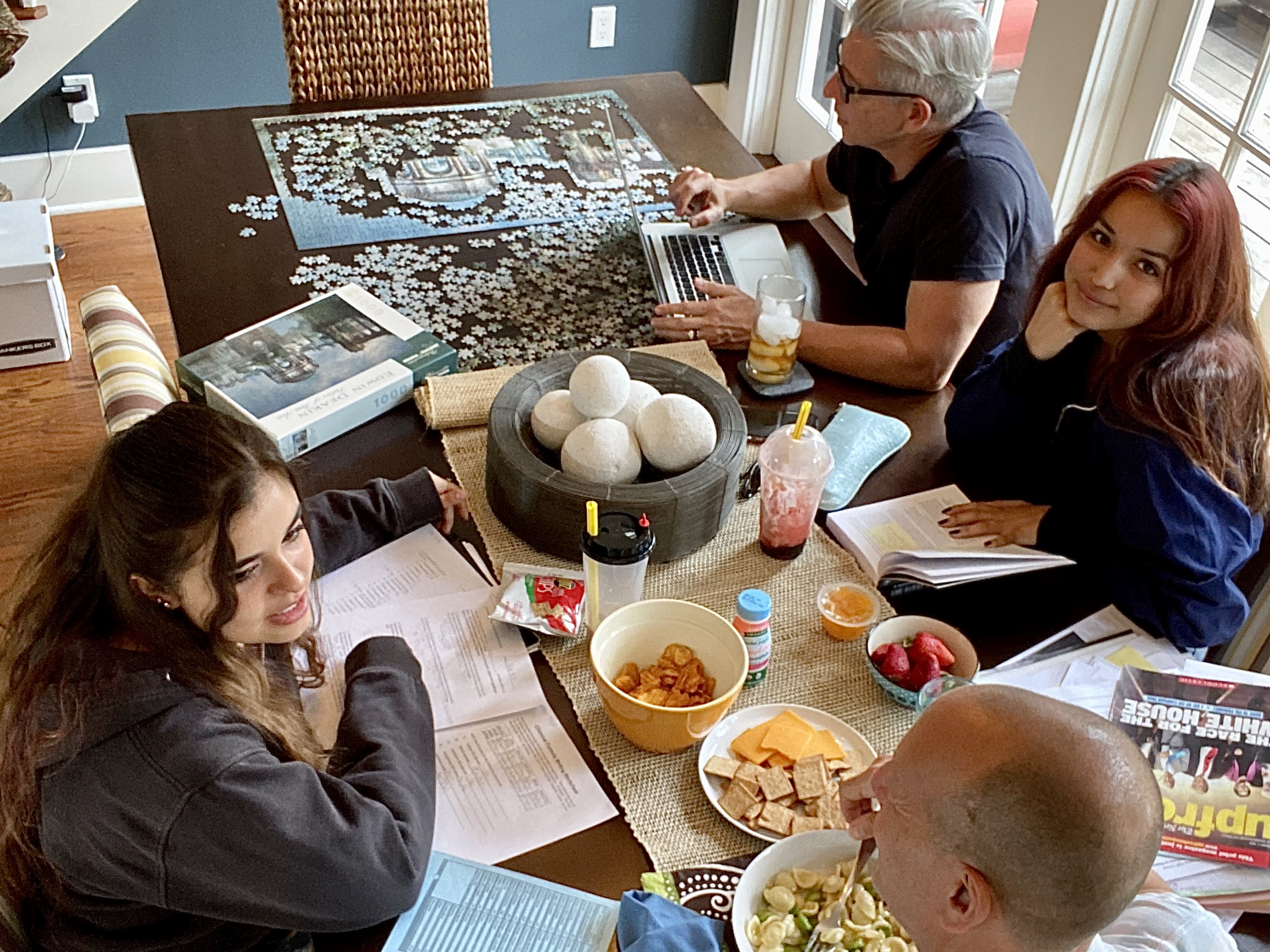 family multi-tasking at dinner table during COVID with food, jigsaw puzzle, homework and laptops.